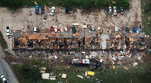 In this aerial photo, law enforcement and rescue personnel search the damage to an apartment complex from the explosion of the West Fertilizer plant on Thursday, April 18, 2013, in West, Texas.