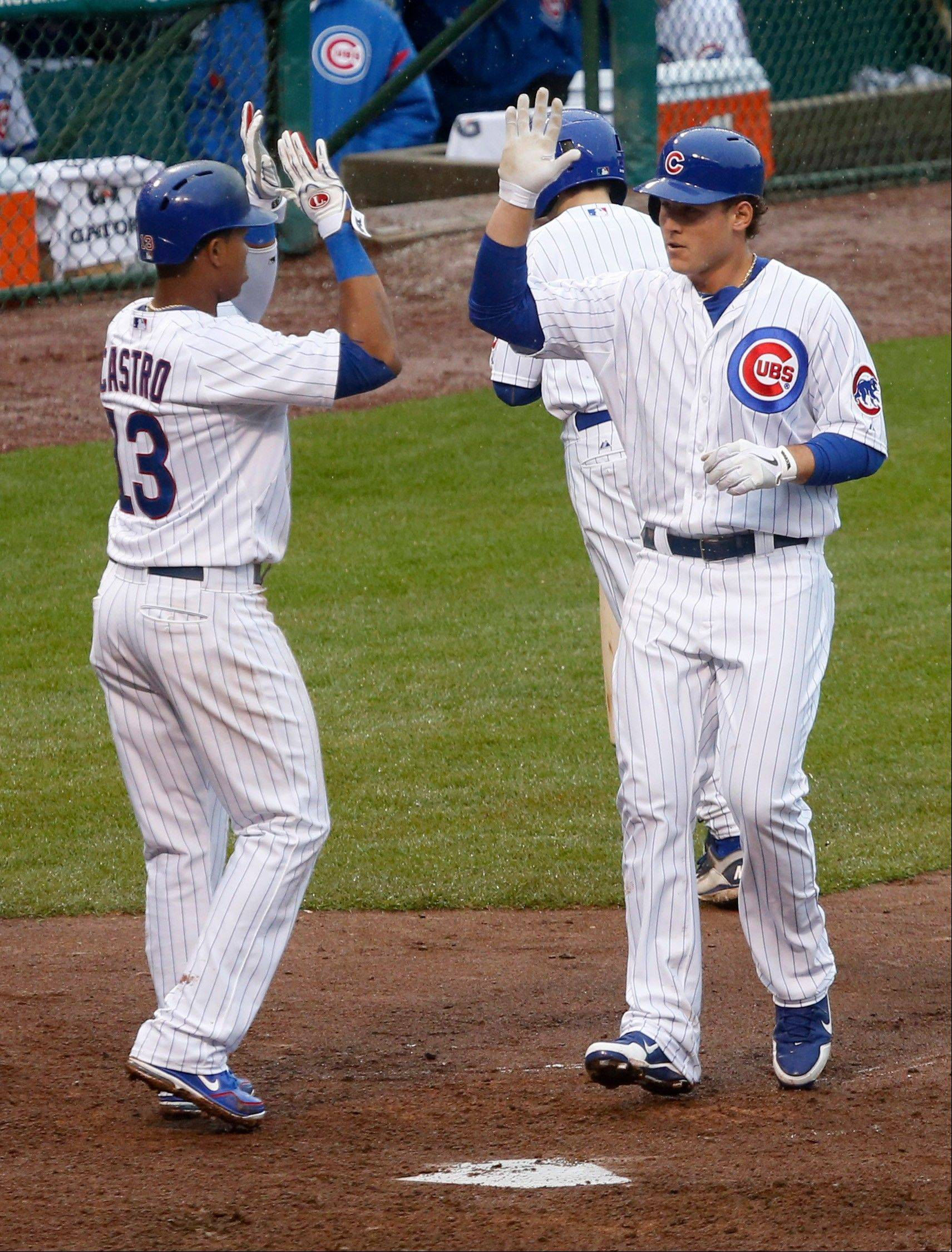 Chicago Cubs' Anthony Rizzo, right is greeted at home by Starlin Castro after the pair scored on Rizzo's home run off Texas Rangers starting pitcher Alexi Ogando during the third inning of a baseball game, Thursday, April 18 2013, in Chicago. (AP Photo/Charlie Arbogast)