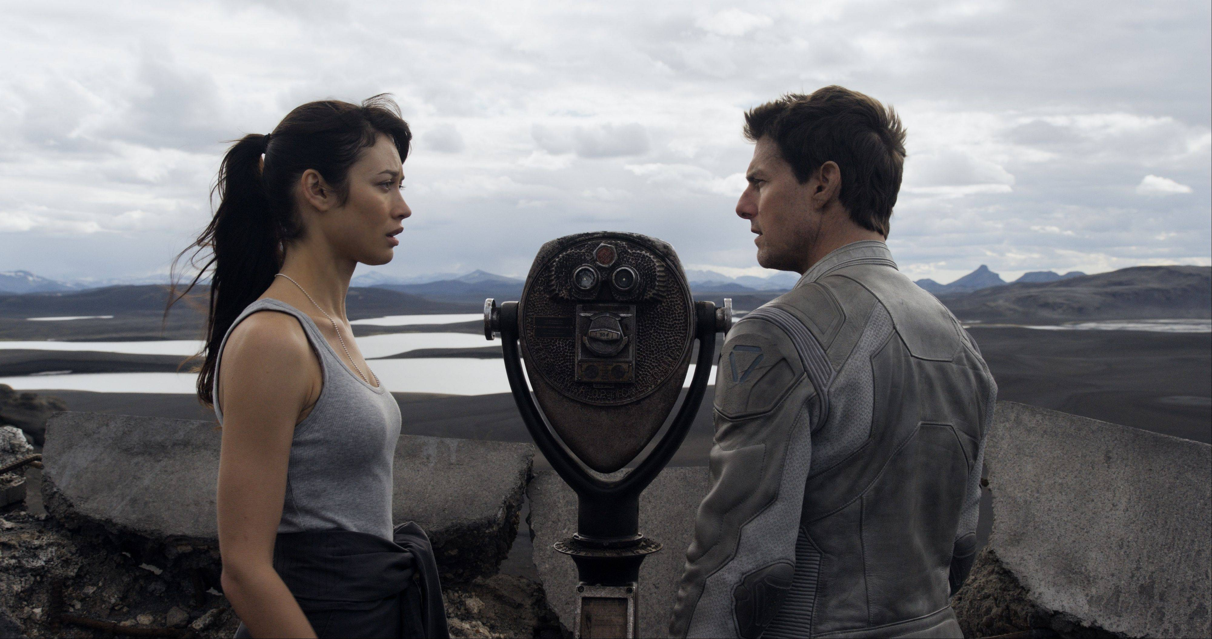 "Julia (Olga Kurylenko) and Jack (Tom Cruise) recreate a memory atop a post-apocalyptic Empire State Building in Joseph Kosinski's science-fiction thriller ""Oblivion."""