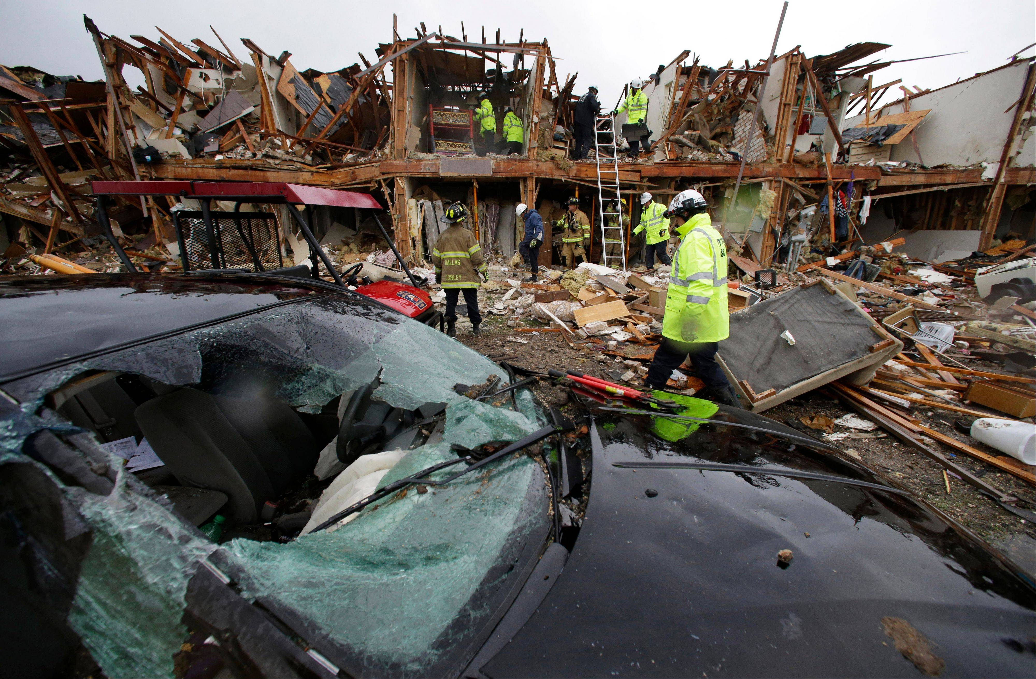 A smashed car sits in front of an apartment complex destroyed by an explosion at a fertilizer plant in West, Texas, as firefighters conduct a search and rescue Thursday. A massive explosion at the West Fertilizer Co. Wednesday night killed as many as 15 people and injured more than 160, officials said overnight.