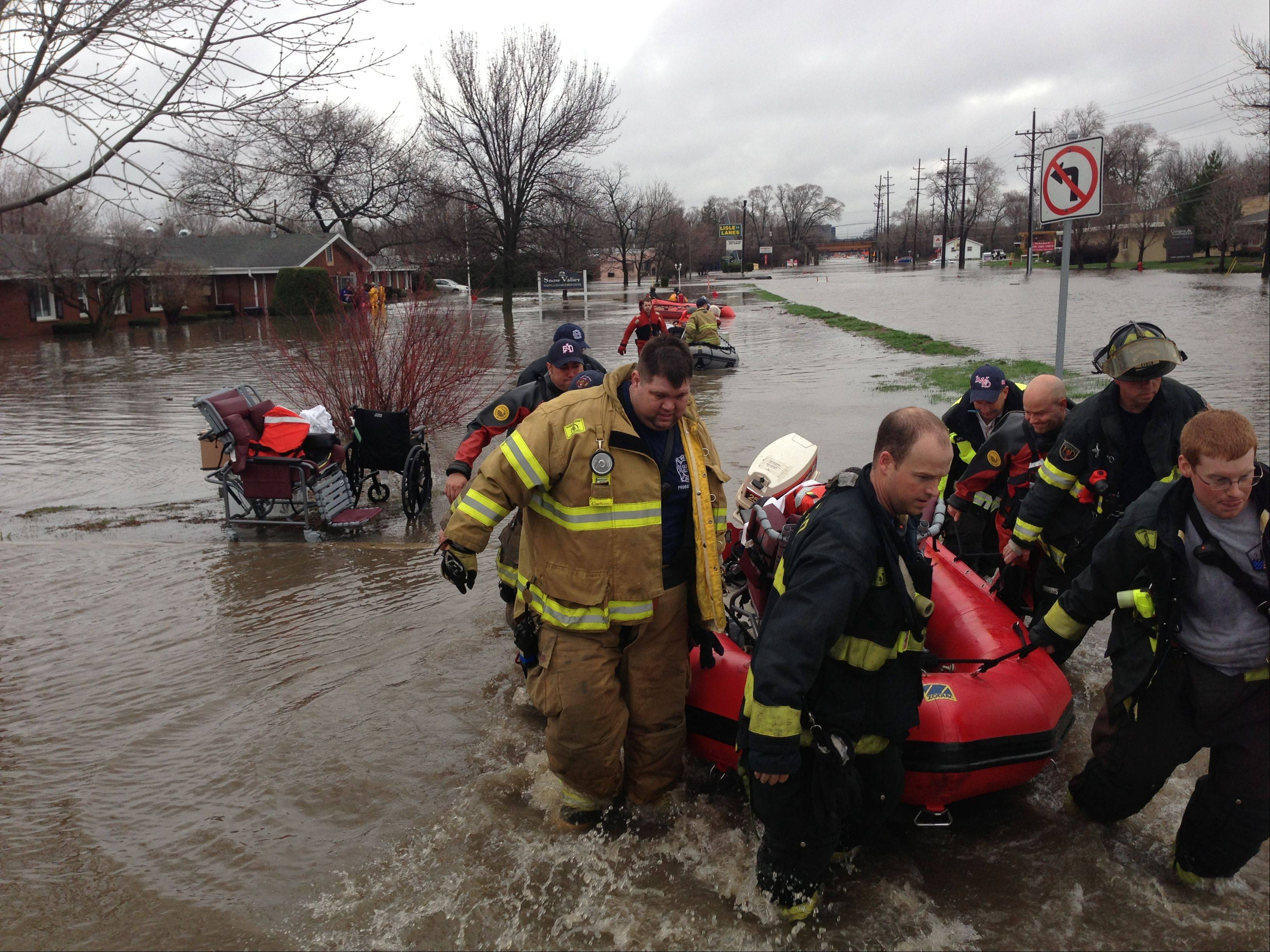 Lisle firefighters carry a resident of the Snow Valley Nursing and Rehabilitation Center in Lisle to safety after floodwaters threatened the facility.