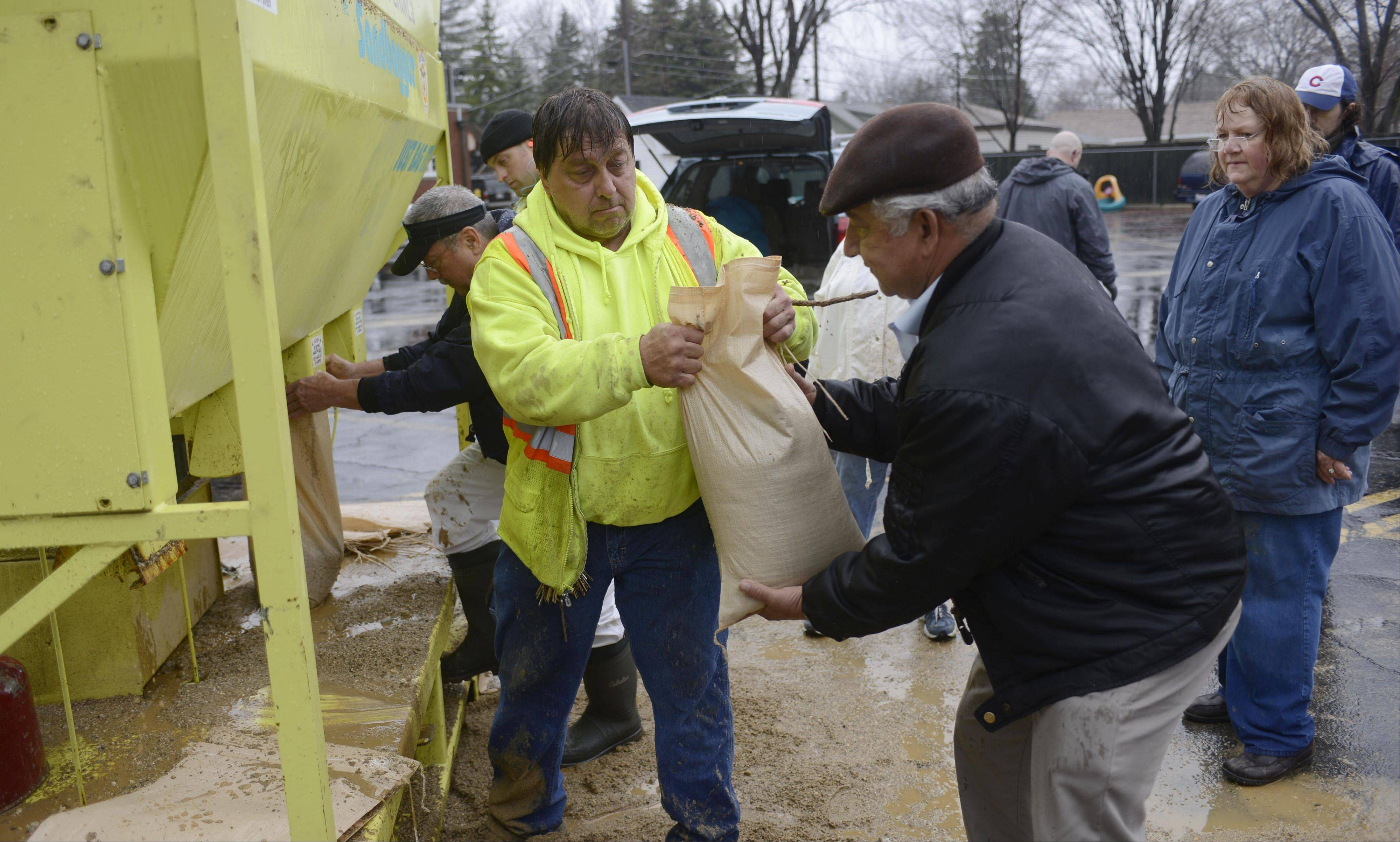 Ray Ritthamel, left, of the Des Plaines Public Works hands a sandbag to resident Sal Castellanos in the parking lot of Christ Church as floodwaters rise in Des Plaines Thursday.