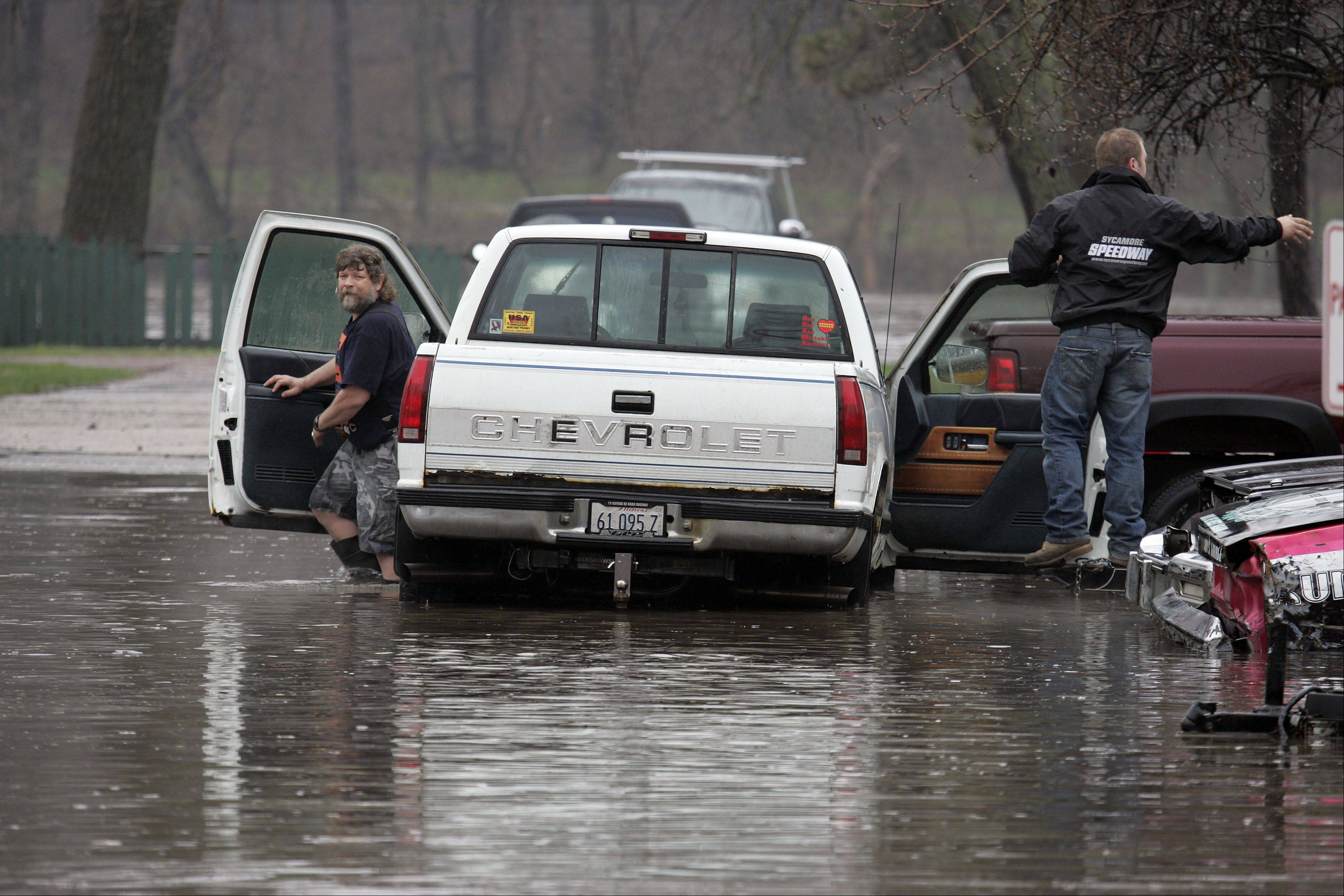 Mike Brancecum of South Elgin, left, and an unidentified man prepare to move one of his vehicles on East Spring Ave in South Elgin after flooding on the Fox River Thursday in South Elgin.