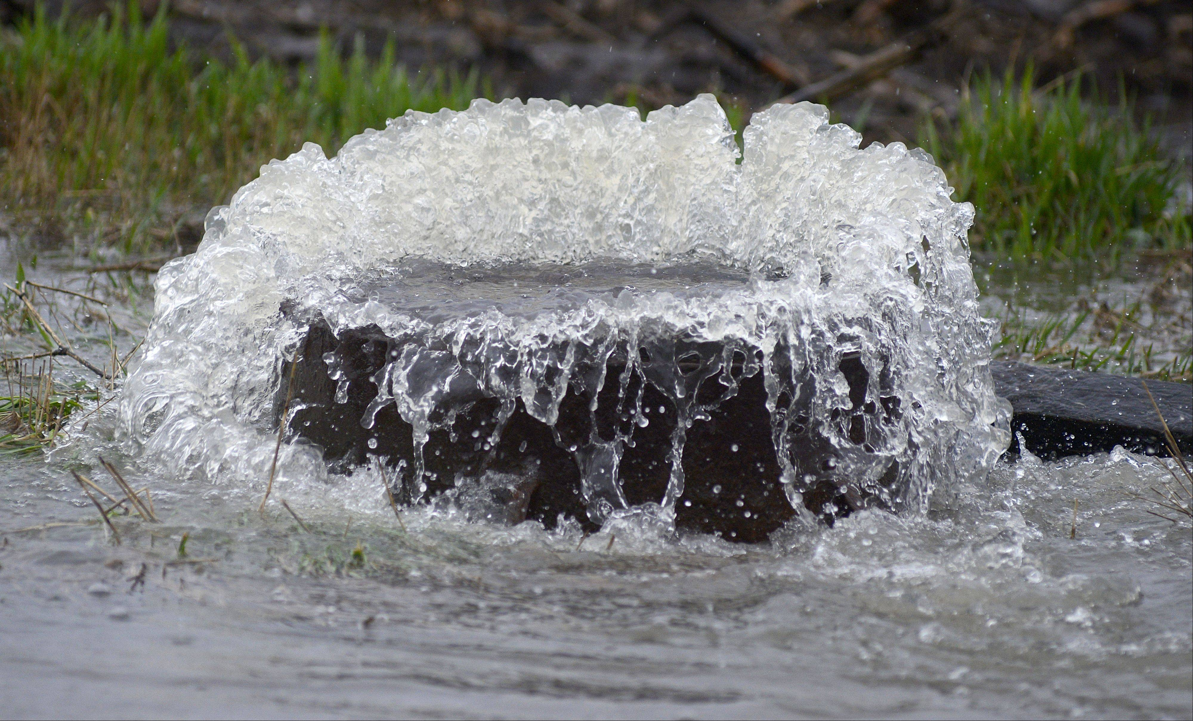 Water bellows from a sewer cap along Route 38 just west of Peck Road in St. Charles on Thursday, April 18.
