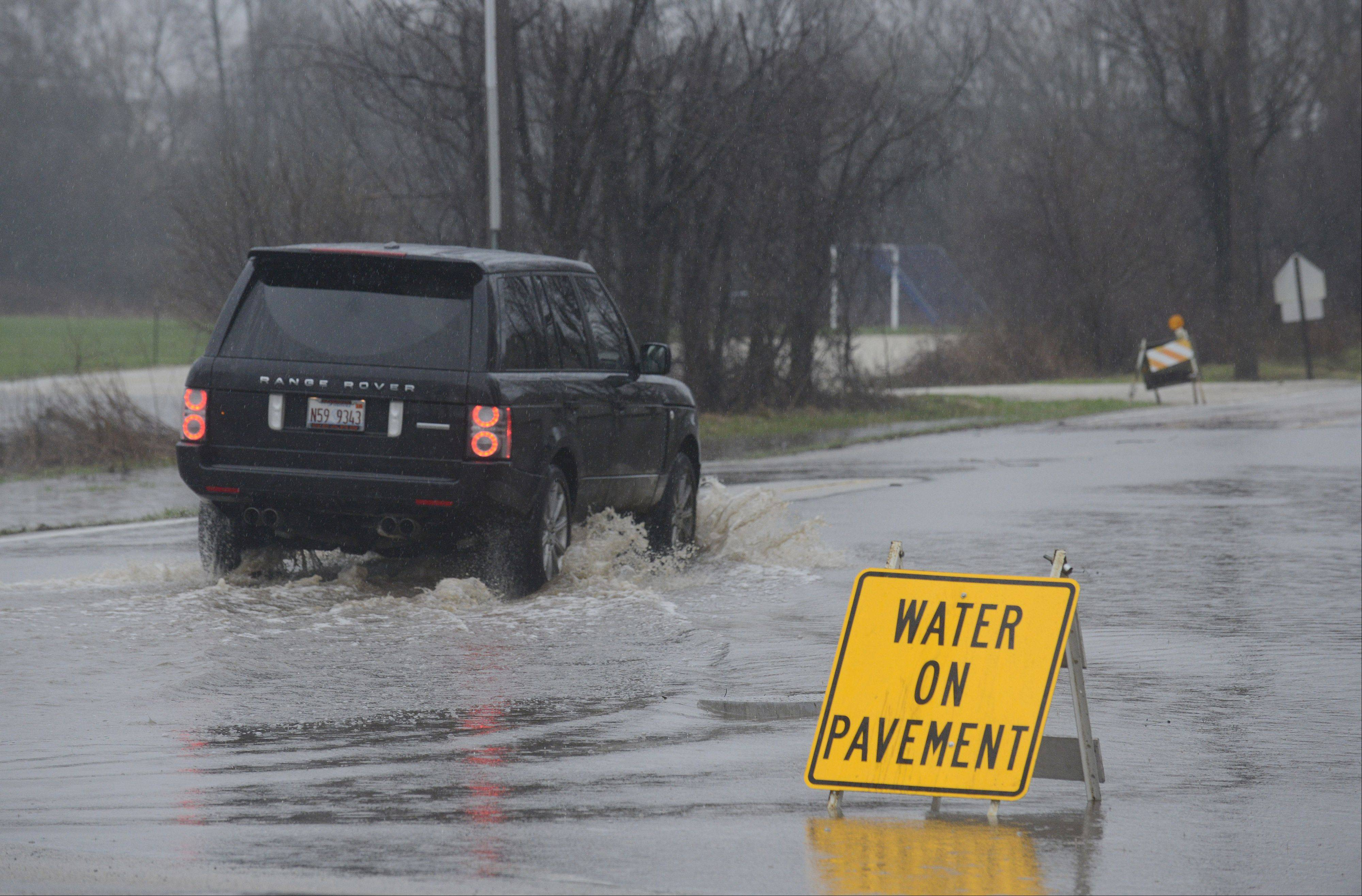 Cars still pass through a rapidly flooding Peck Rd at Dean Street in St. Charles on Thursday, April 18. The north side of the street was flooded allowing only for passage on the south side.
