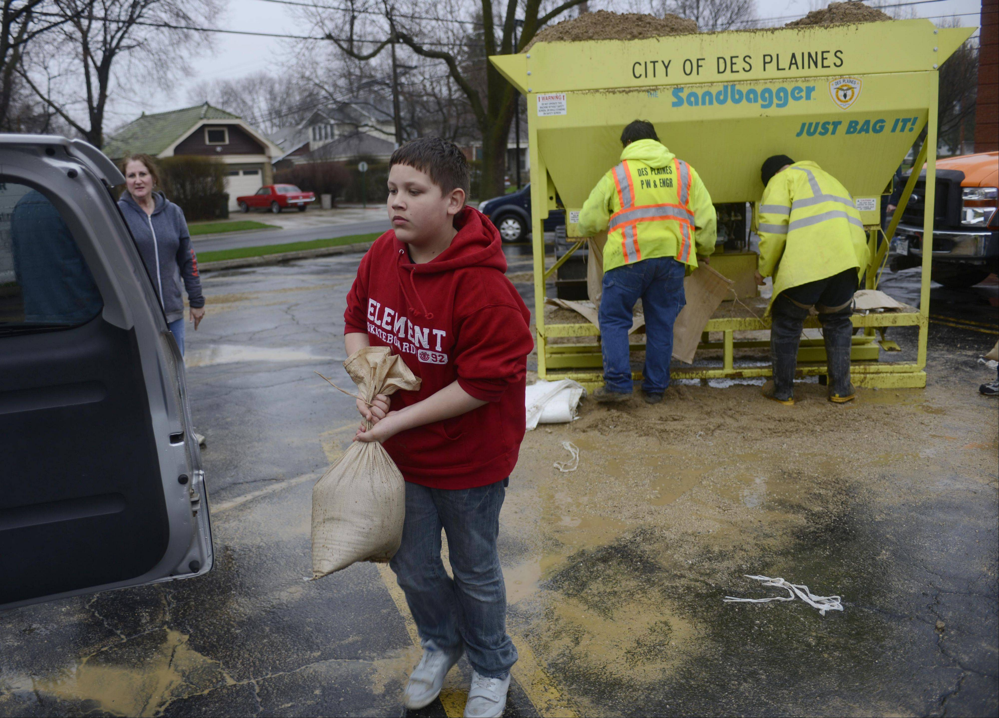 Manny Stewart carries a sandbag from the public works loading operation at the Christ Church parking lot to his mom's van as floodwaters rise in Des Plaines Thursday.