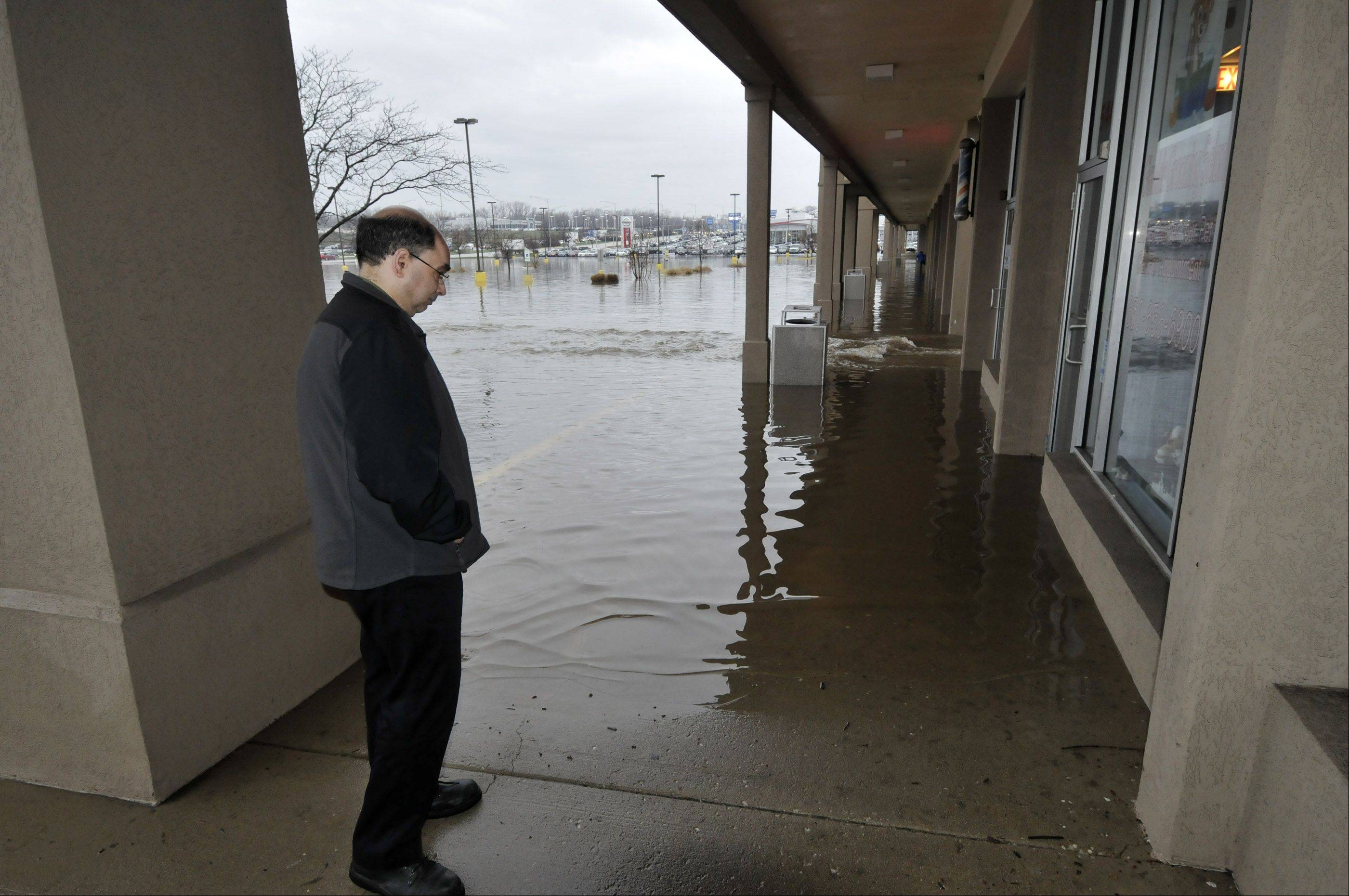 Bob Pellicane looks at the flooding that is preventing him from getting to his job at Dollar General in Glendale Heights. Several businesses at North Ave. and Glen Ellyn Rd. were under water, including Glendale Grooming Salon, and a barber shop next door. Heavy rains overnight resulted in heavy flooding in the DuPage County area.
