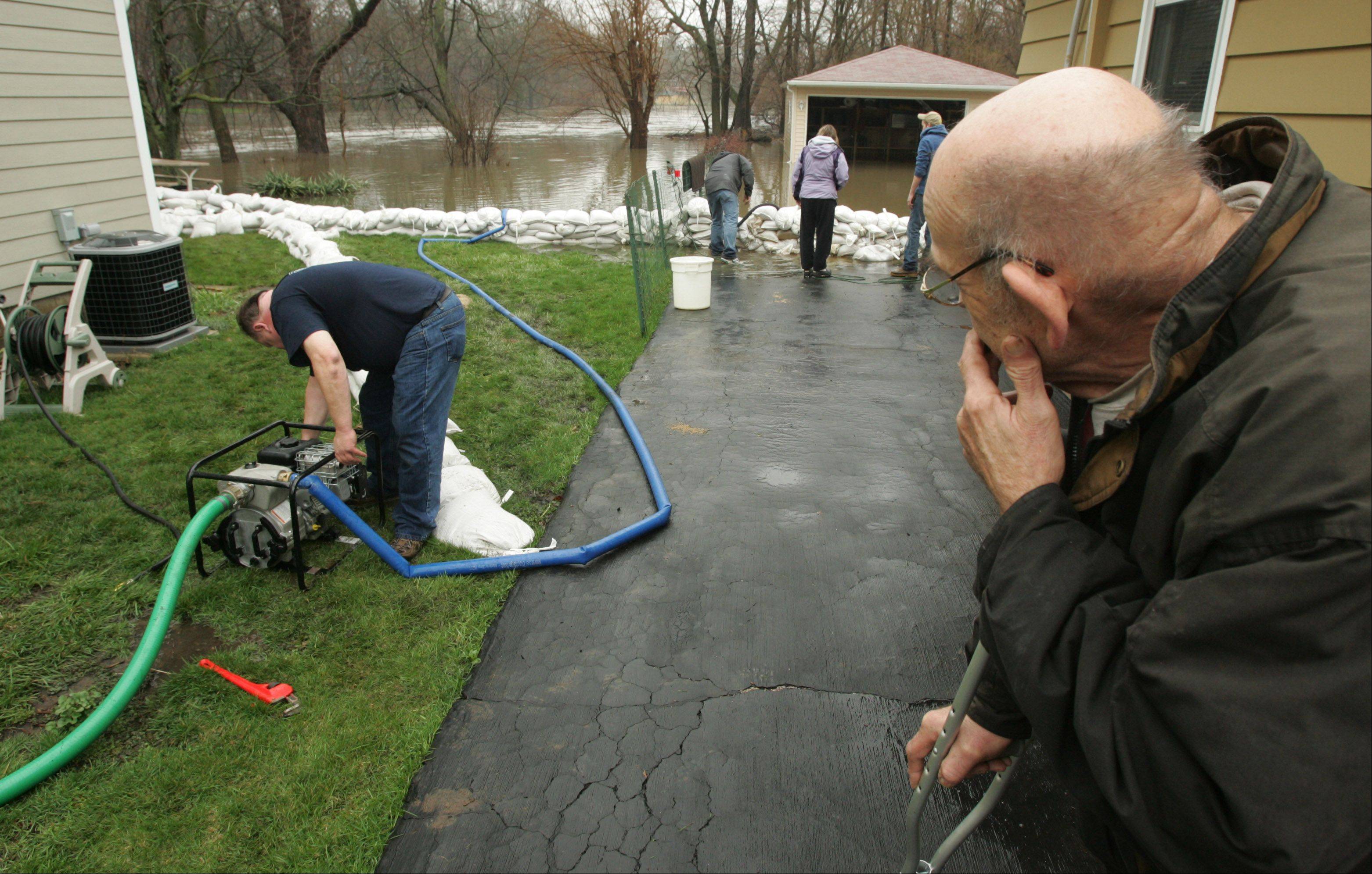 Algonquin resident Roger Baumgartner watches as his neighbor Tony Angarola gets a pump fired up to get water out of his crawl space Thursday morning along Willow Street near the Fox River.