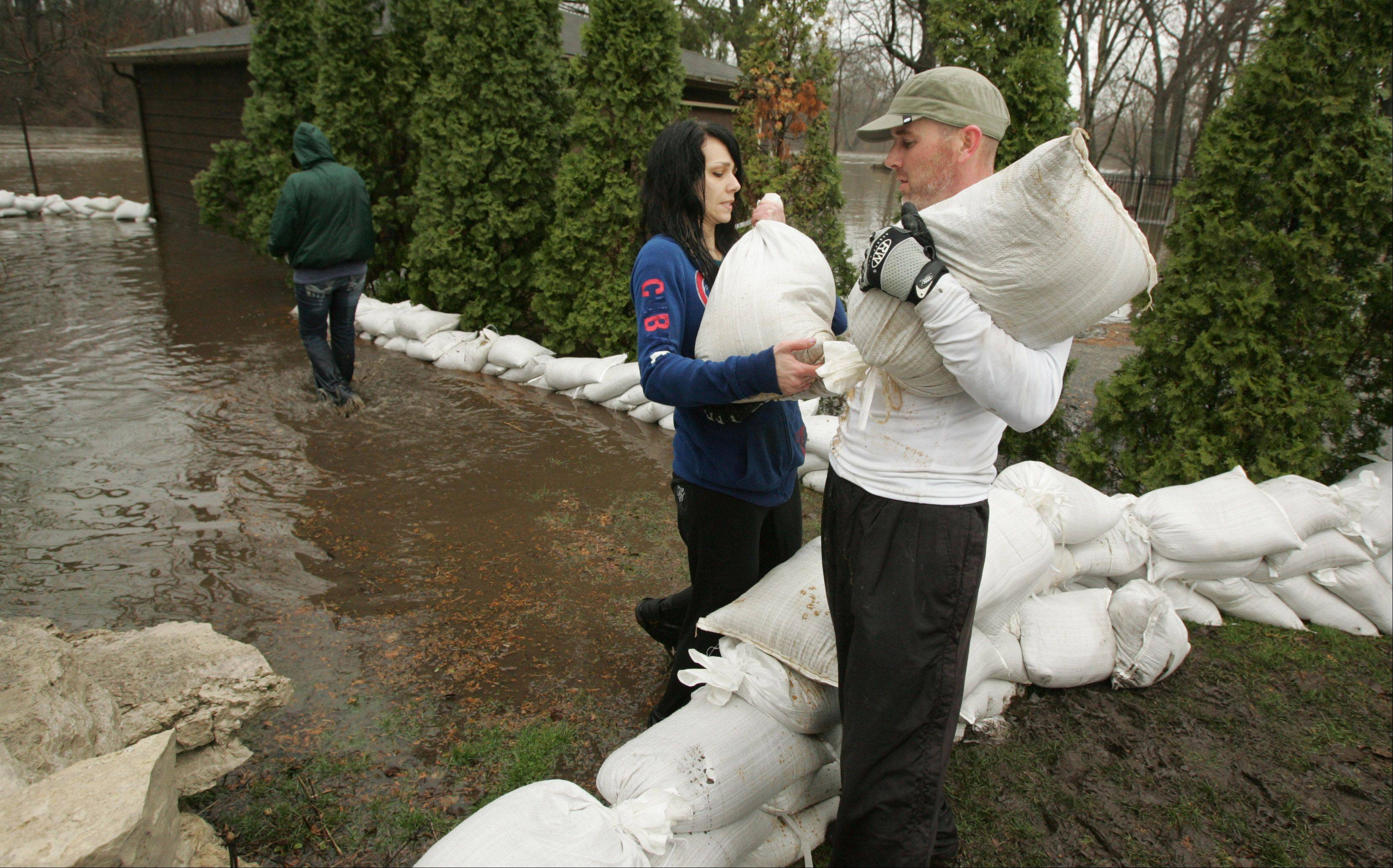 Algonquin resident David Bateman hands a sand bag to Corinne Breskovich of Crystal Lake as they join with other to protect a home along the Fox River in Algonquin Thursday morning.