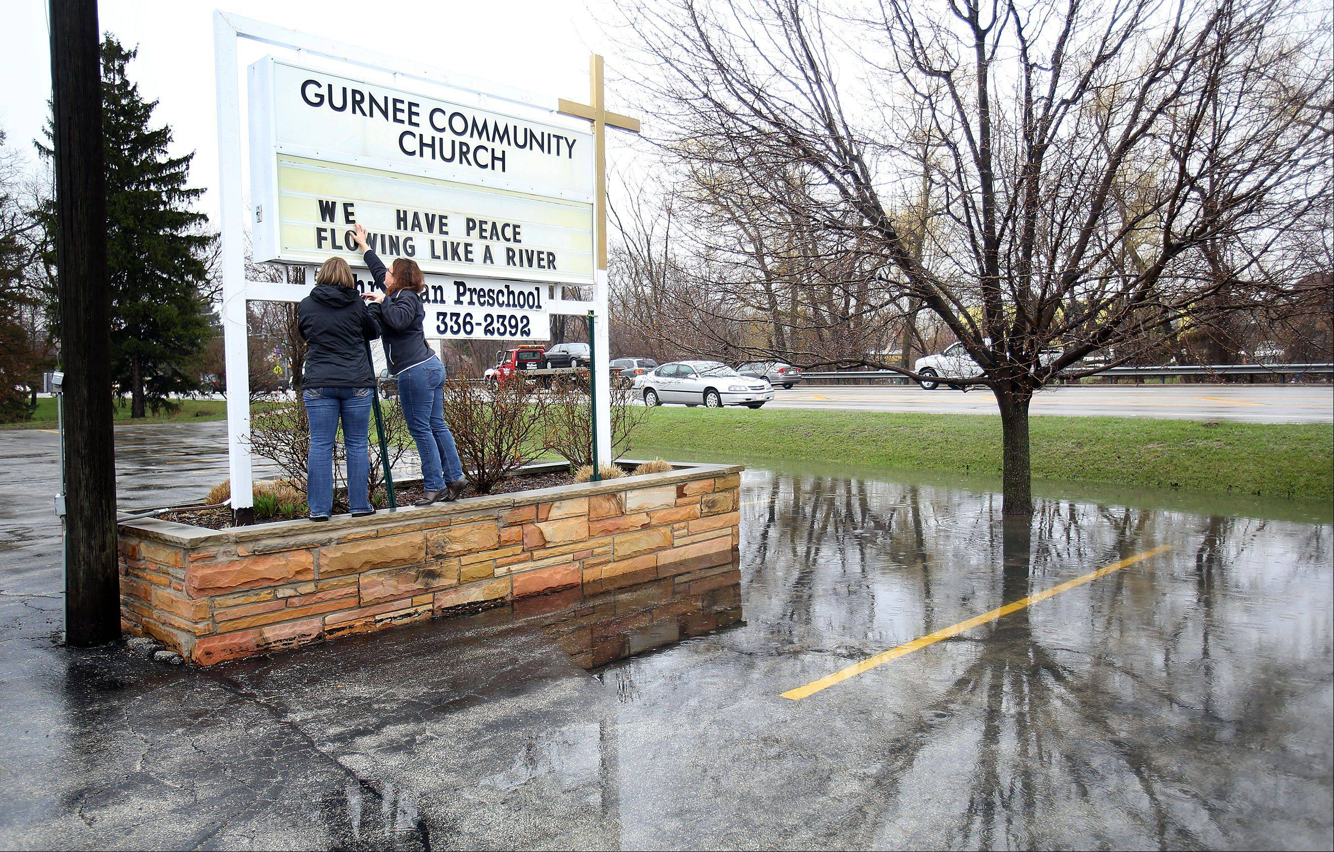 "Gurnee Community Church employees Stacey Rowan, left, and Shawn Robards make a sign that says ""We have peace flowing like a river"" as they prepare for flooding in Gurnee Thursday morning."