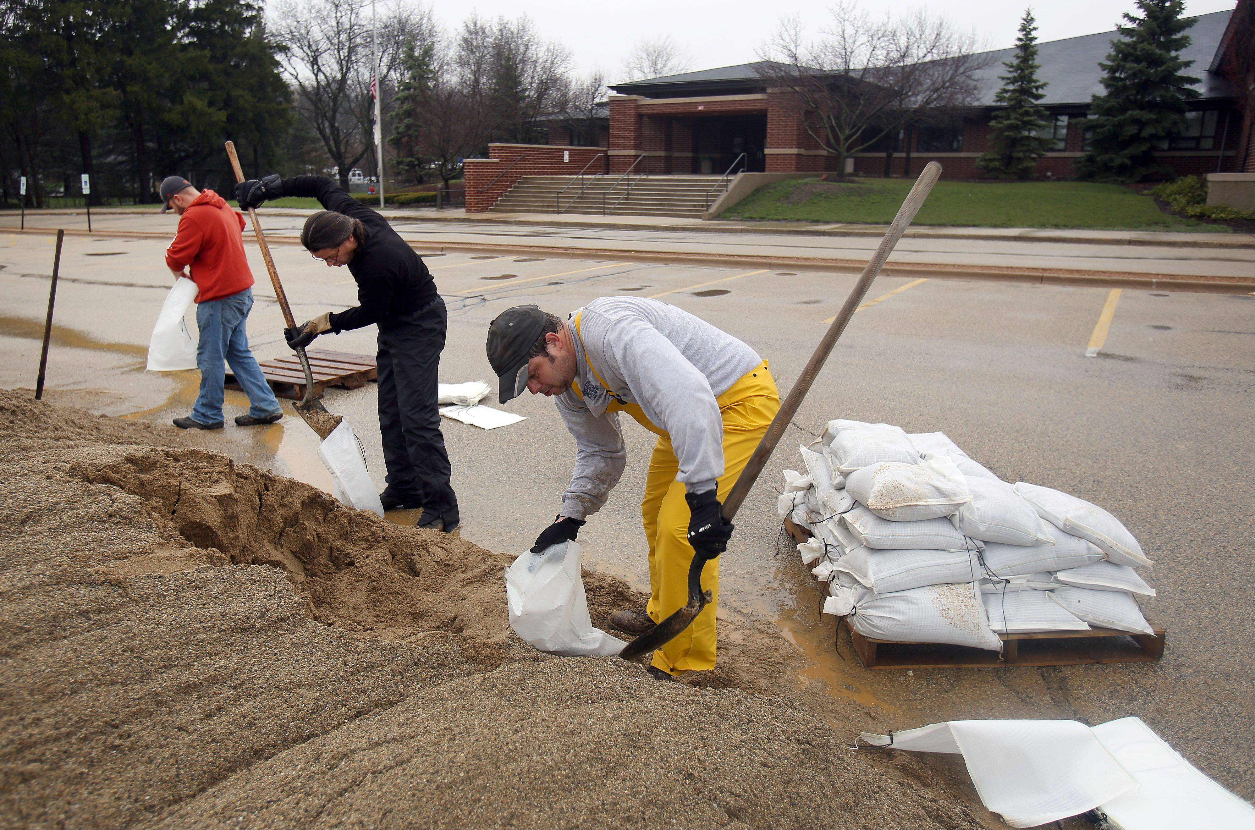 Volunteers from left, David Gonzalez, Mark Horvat and Eric Sindermann, all of Gurnee, help sand bag in front of Viking School in preparation for flooding in Gurnee Thursday morning.