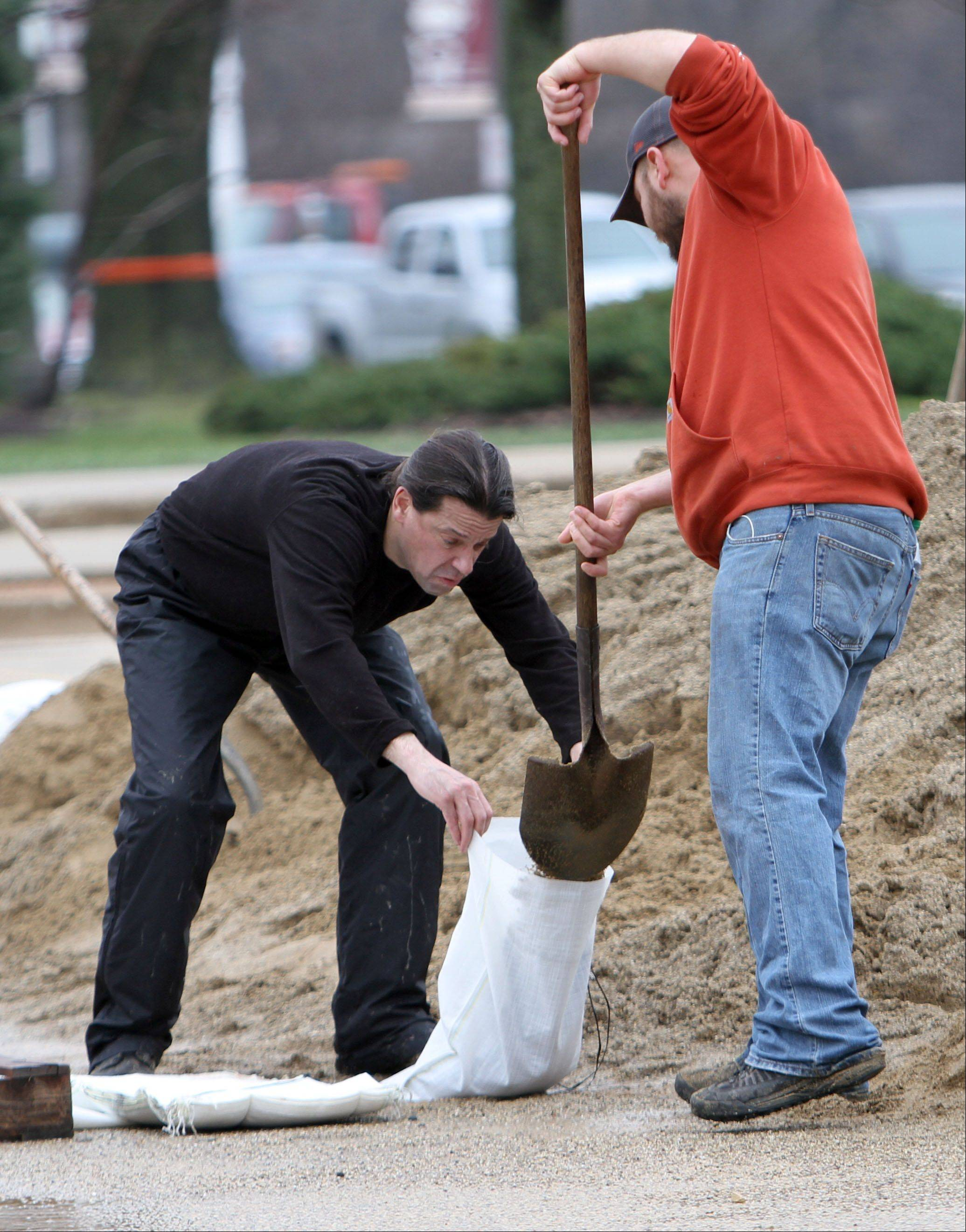 Volunteers Mark Horvat, left, and David Gonzalez, both of Gurnee, help sand bag in front of Viking School in preparation for flooding in Gurnee Thursday morning.
