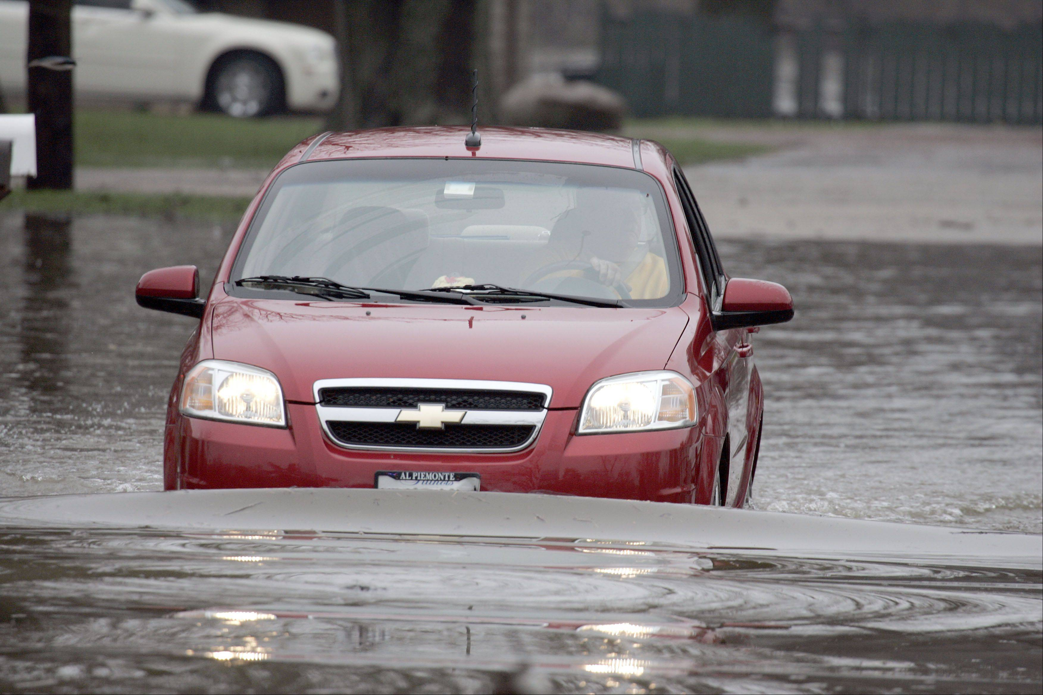 An unidentified man attempts to drive his car down East Spring Ave after flooding on the Fox River Thursday in South Elgin.
