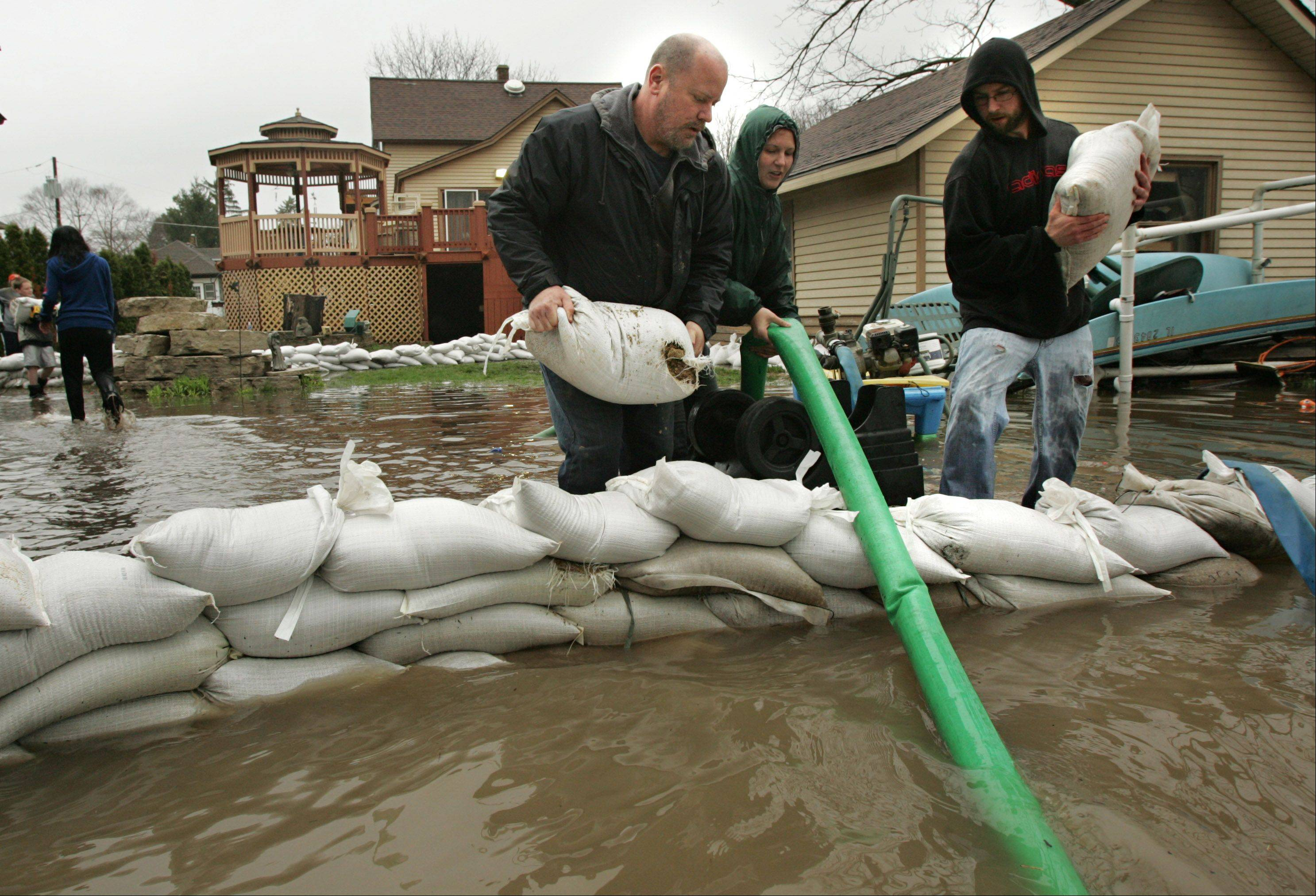 Algonquin resident Greg Stone, left, gets some help sandbagging his father-in-law's backyard along the Fox River from his wife Courtney, center, and Lake in the Hills resident Eric Johnson. Johnson was nearby taking pictures at Towne Park and offered to help the nearby residents trying to protect their homes.