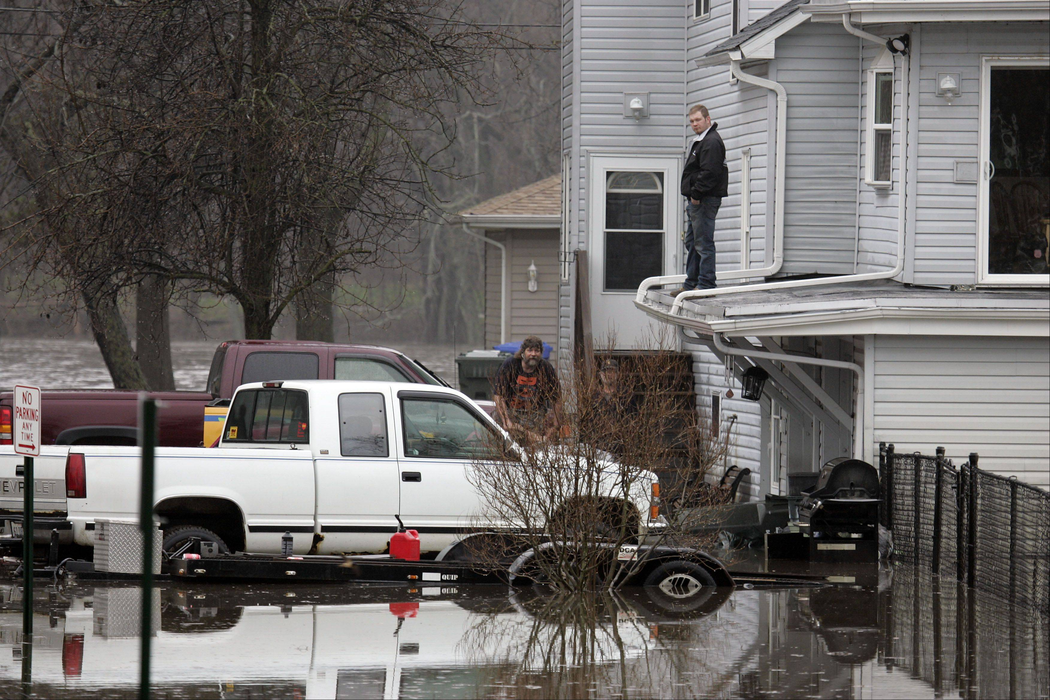Mike Brancecum of South Elgin, behind truck, and an unidentified man on the roof watch as water attempts to invade his home on East Spring Ave in South Elgin Thursday.