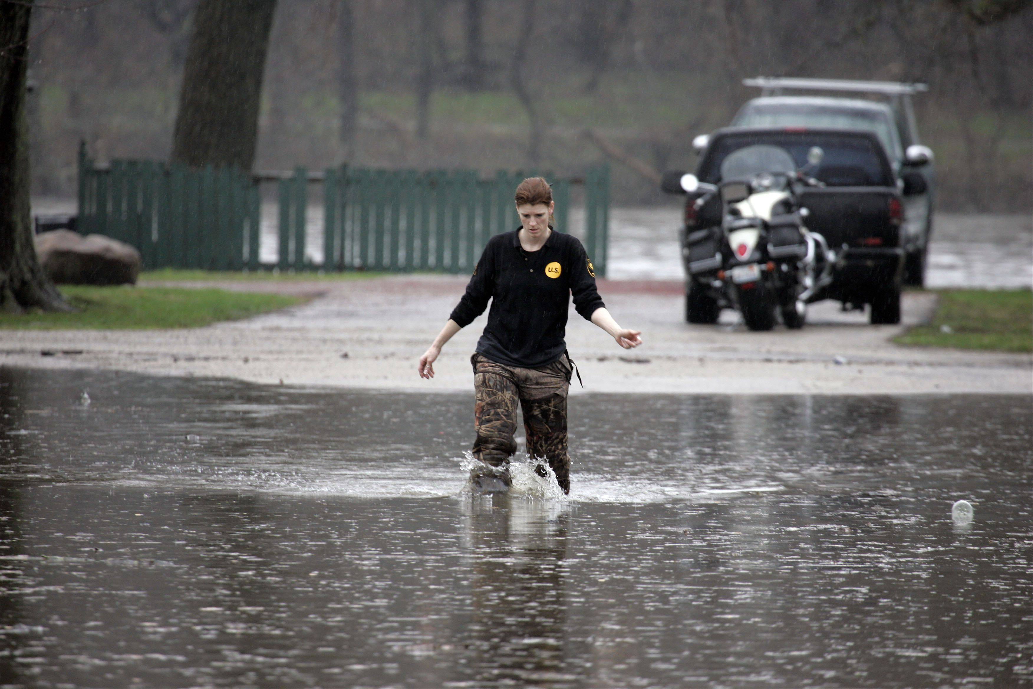 Carrie Wolotowsky of South Elgin wades across a flooded East Spring Ave to get to her vehicle after flooding on the Fox River Thursday in South Elgin.