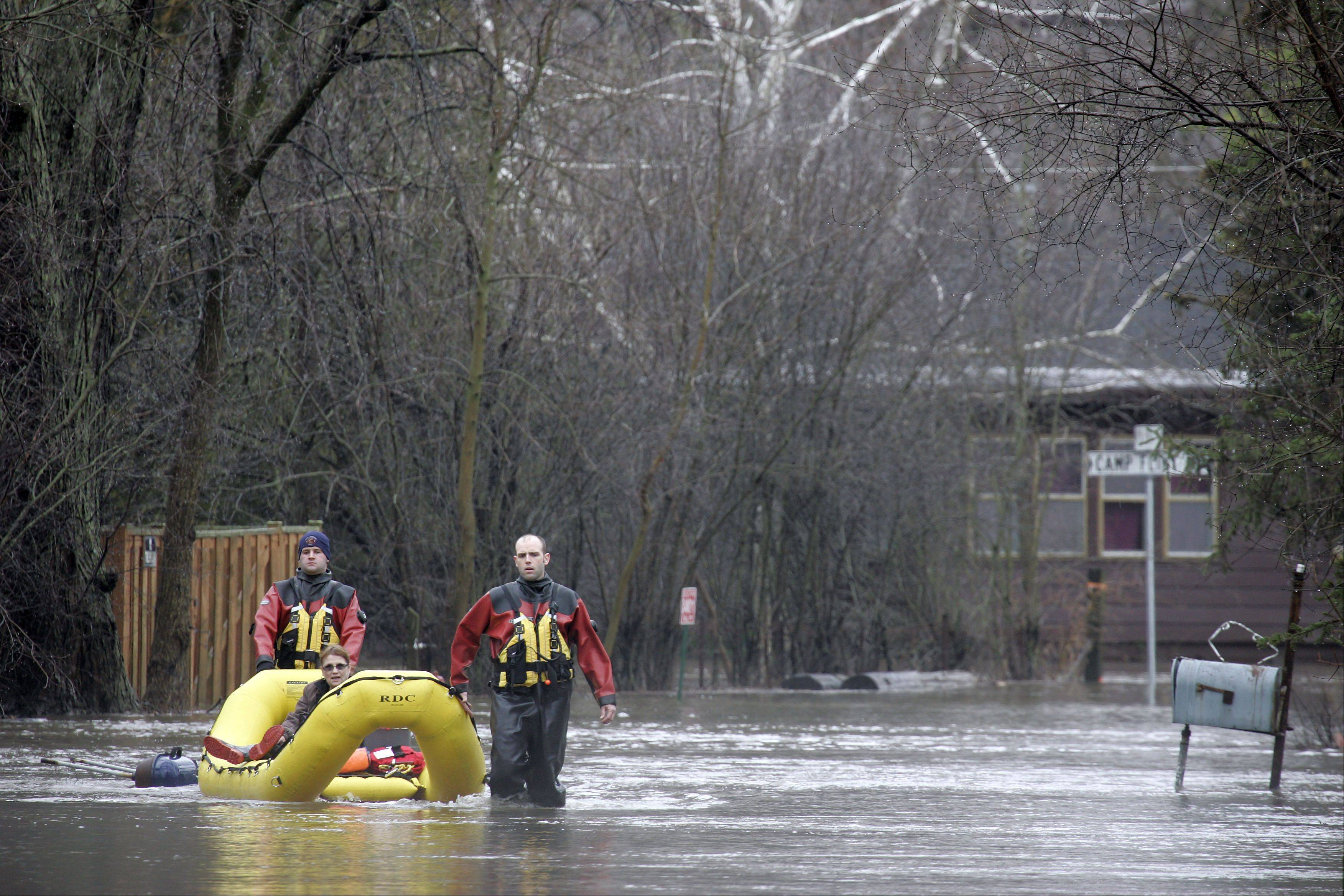 "East Dundee firefighter Nick Beauchaine, left, and lieutenant Jason Parthun, help Barrie Komorski and her dog Roxi from her home along Fox River Drive after flooding on the Fox River caused voluntary evacuation Thursday in East Dundee. ""I normally would have stayed but the shut off the gas so I had to leave because of my dog Roxi"" Komorski said."