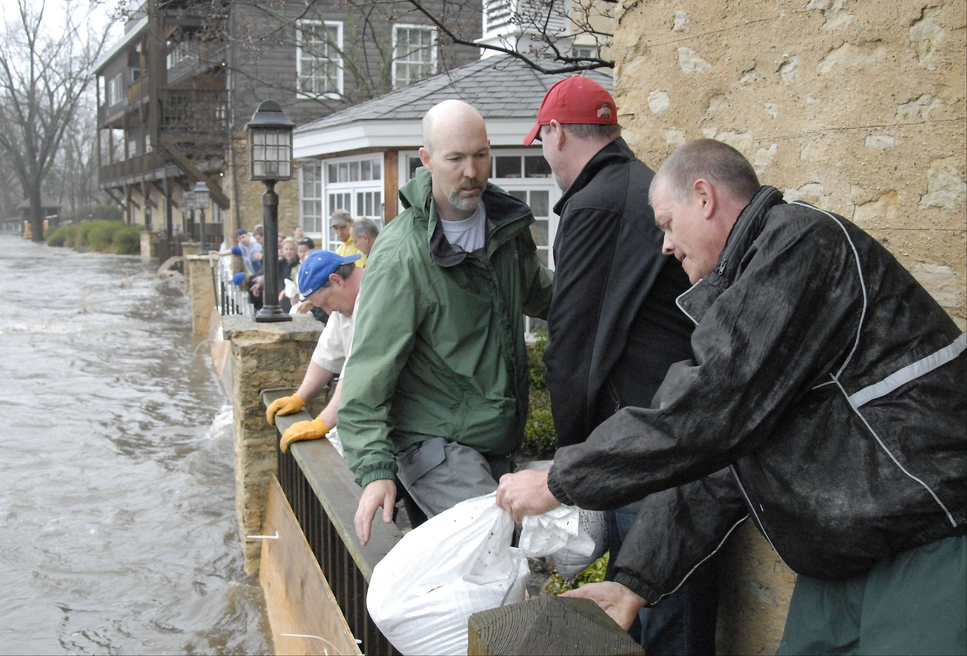 Herrington Inn owner Paul Ruby passes volunteer sandbaggers Chris Schmedes of Geneva and Brad Umholtz of South Elgin as they try to stop the Fox River from flooding the Geneva hotel on Thursday, April 18. Ruby put out the call for help early and people came by the dozens to help out. Many said that Ruby has helped the community so much and it was their turn to help him.