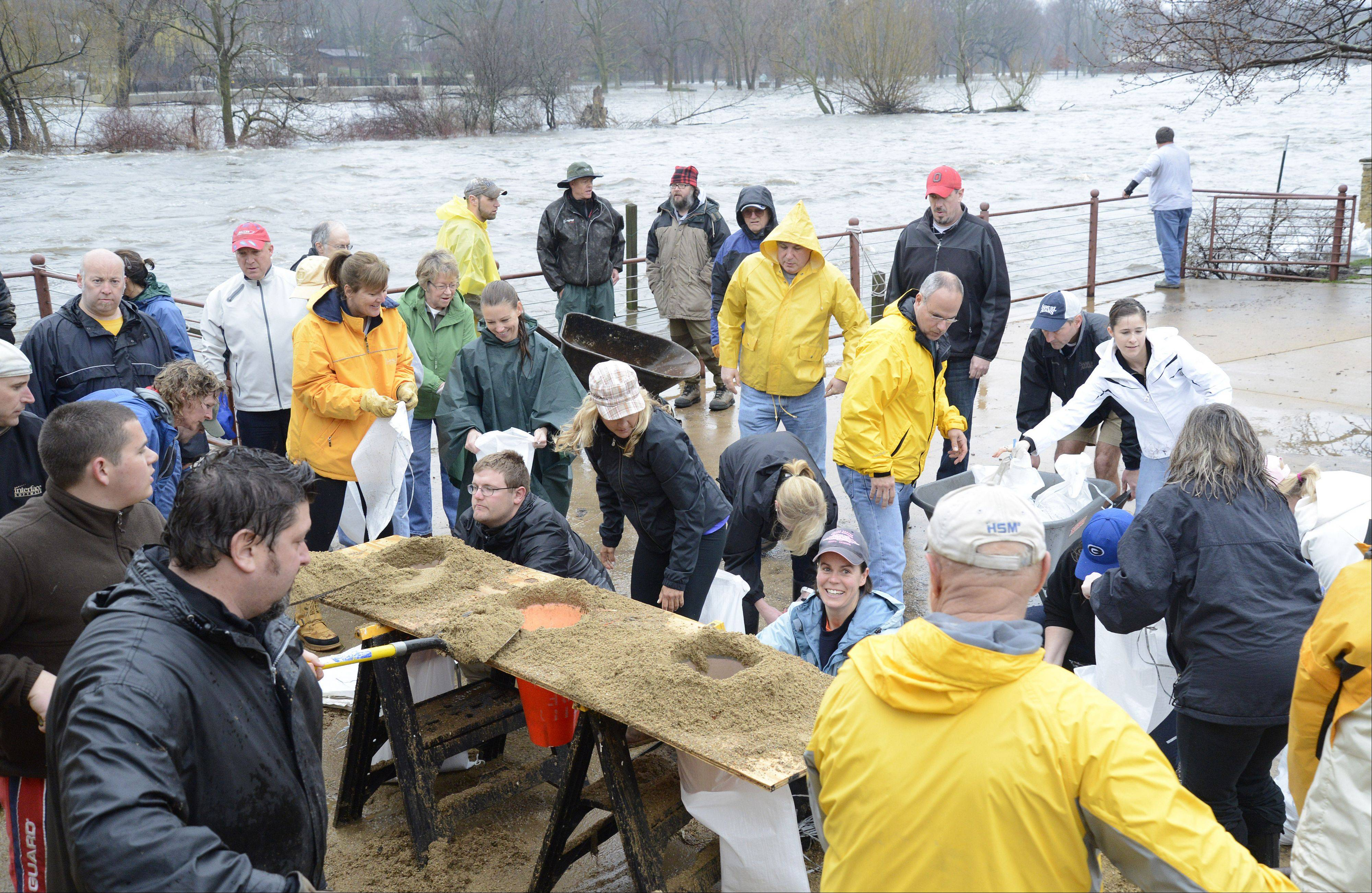 Volunteers help fill bags to block the floodwaters from entering the Herrington Inn in Geneva on Thursday, April 18.