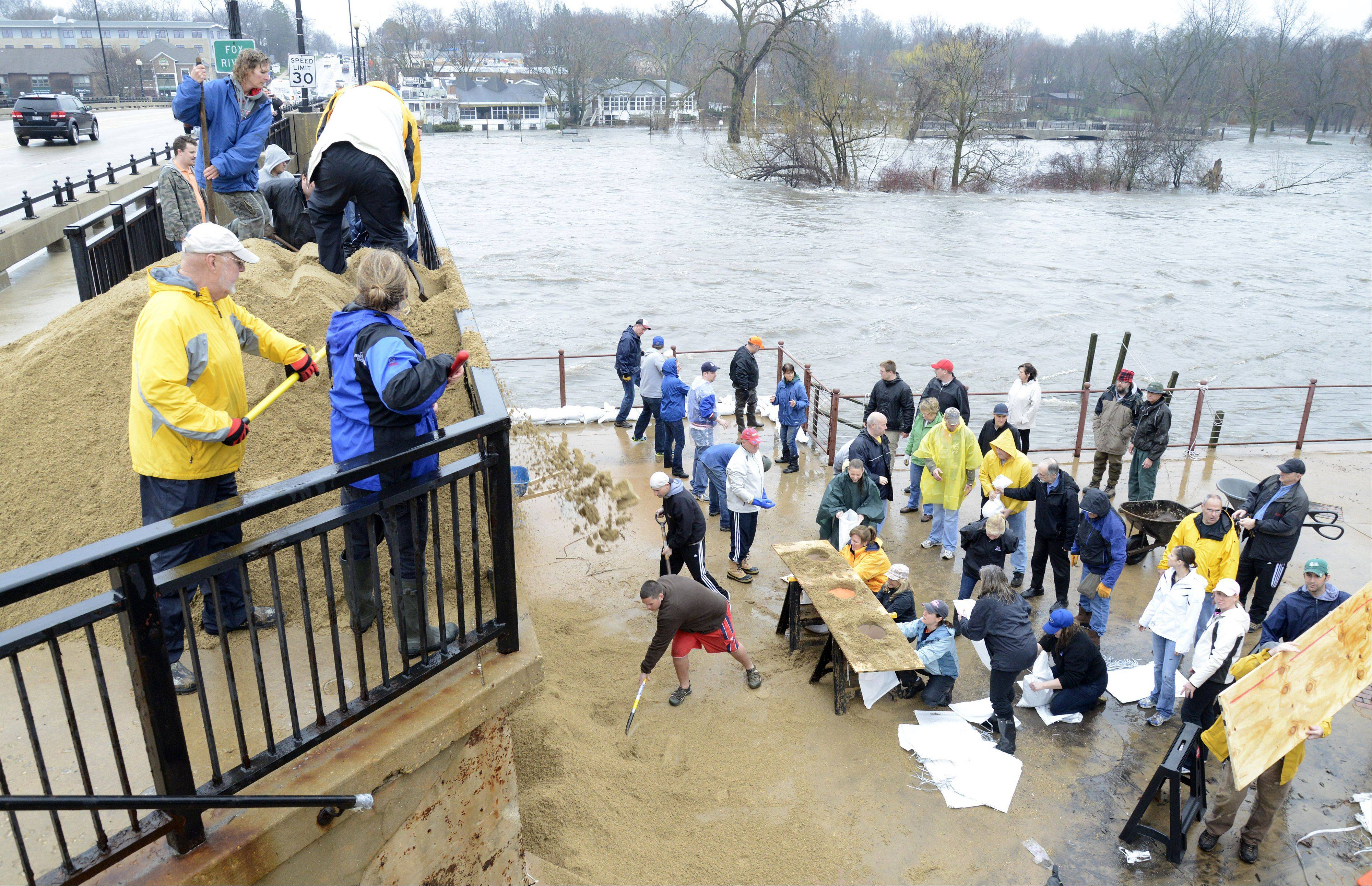 Volunteers came out by the dozens to help stop the Fox River floodwaters from entering the Herrington Inn in Geneva on Thursday, April 18. Semi loads of sand were dumped on the State Street Bridge and volunteers would shovel it down over the edge of the bridge to the baggers.