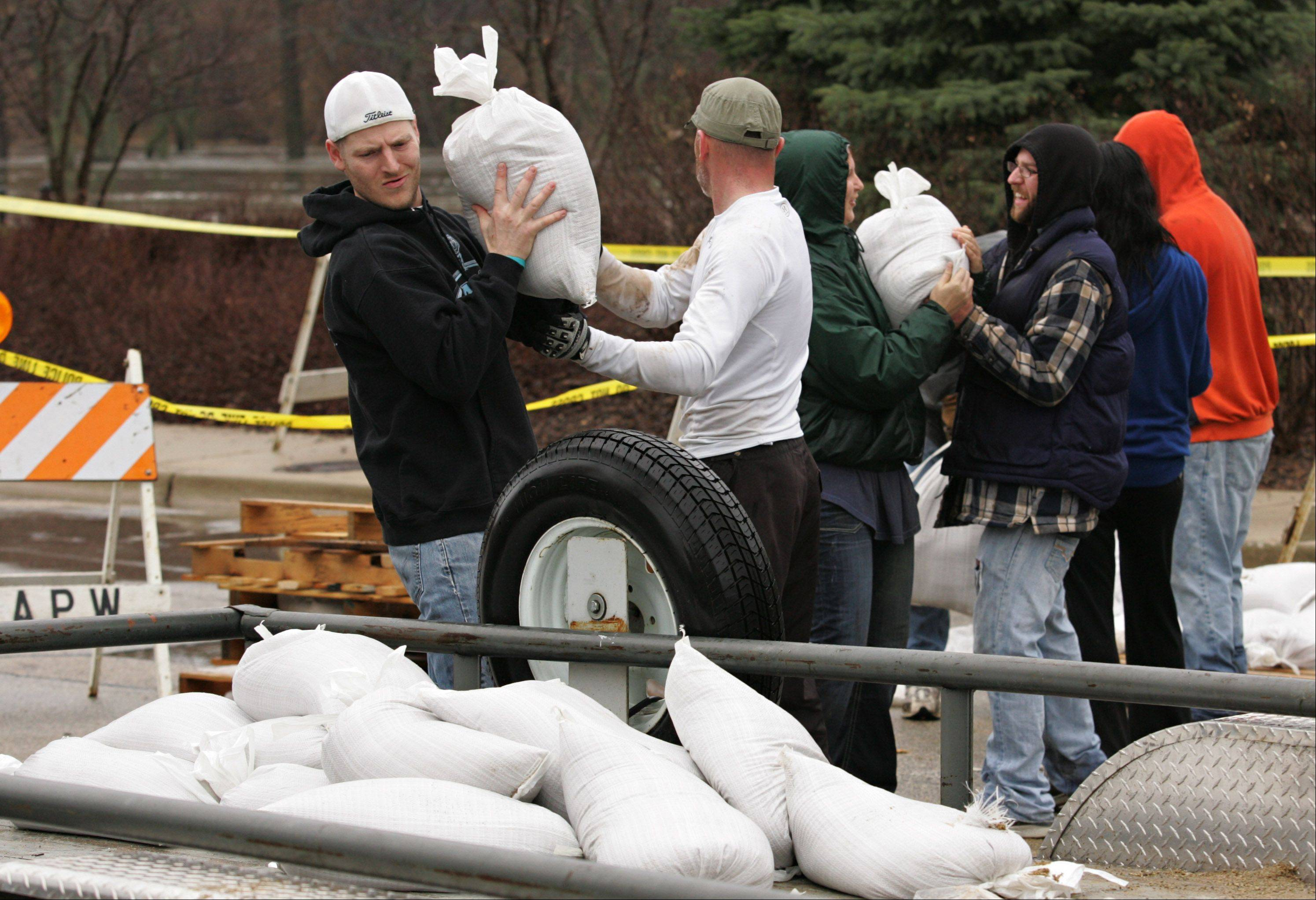Algonquin resident Kevin Prokop loads more sand bags into a trailer to be used in nearby backyards to protect against the rising waters of the Fox River.