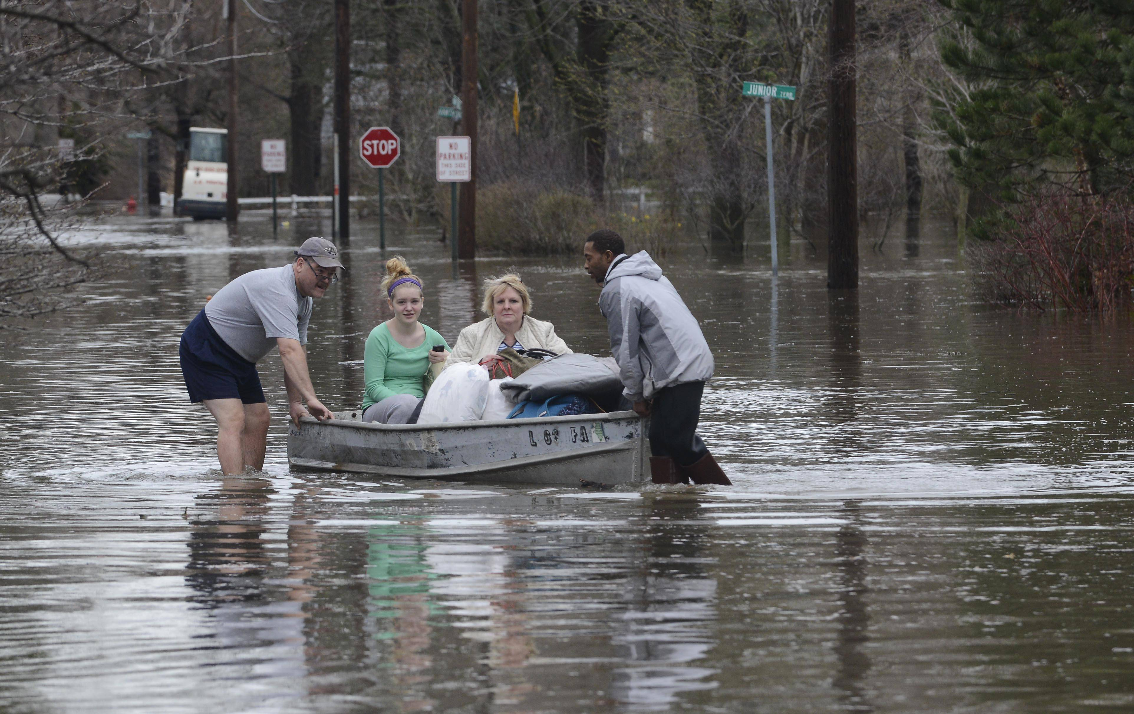 Ted Tworek, left, helps his daughter, Alison, and wife Donna, get to higher ground with the assistance of Antonio Tenner in the flooded Big Bend neighborhood in Des Plaines Thursday as the Des Plaines River continues to rise.