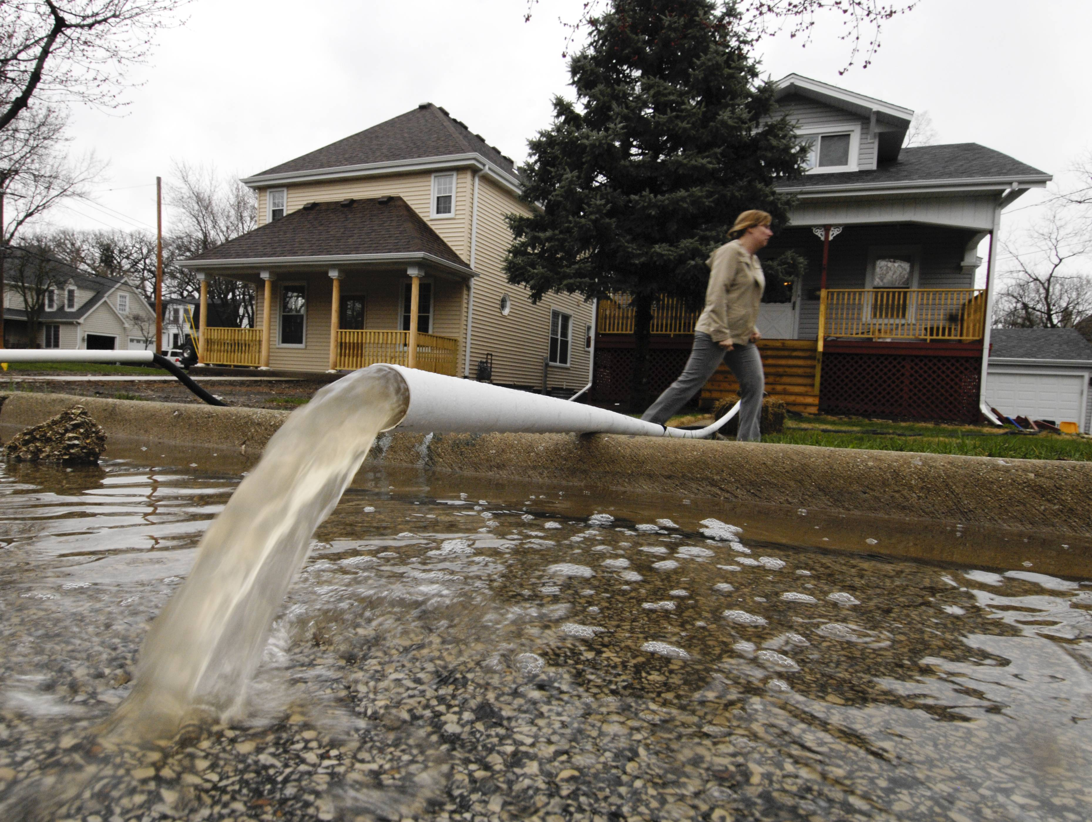 Home owners along Elizabeth Street pumped water from their homes into the street Thursday in Lombard.
