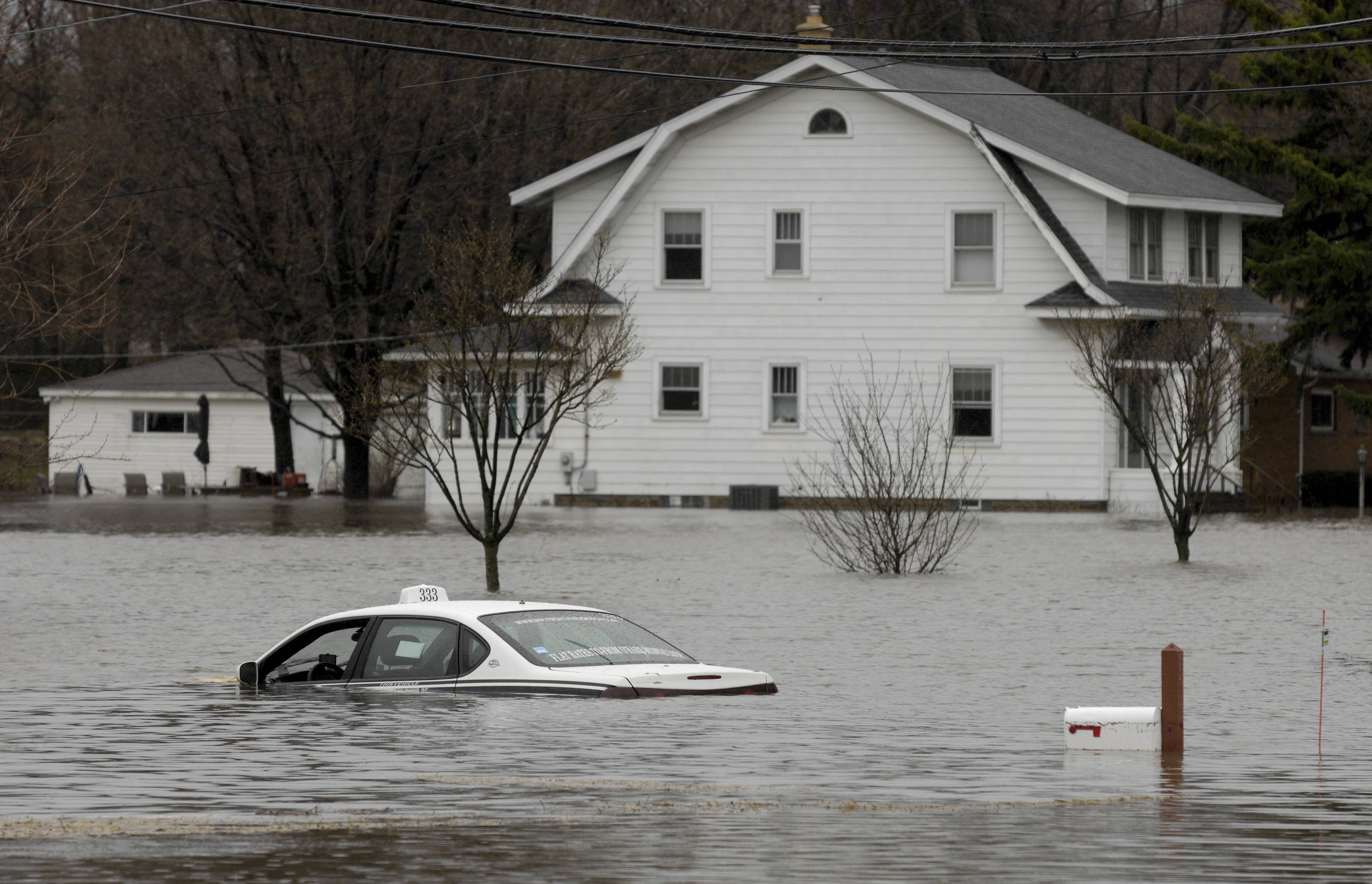 A taxi sits flooded up to the windows along Finley Road  near Charles Lane in Lombard Thursday.