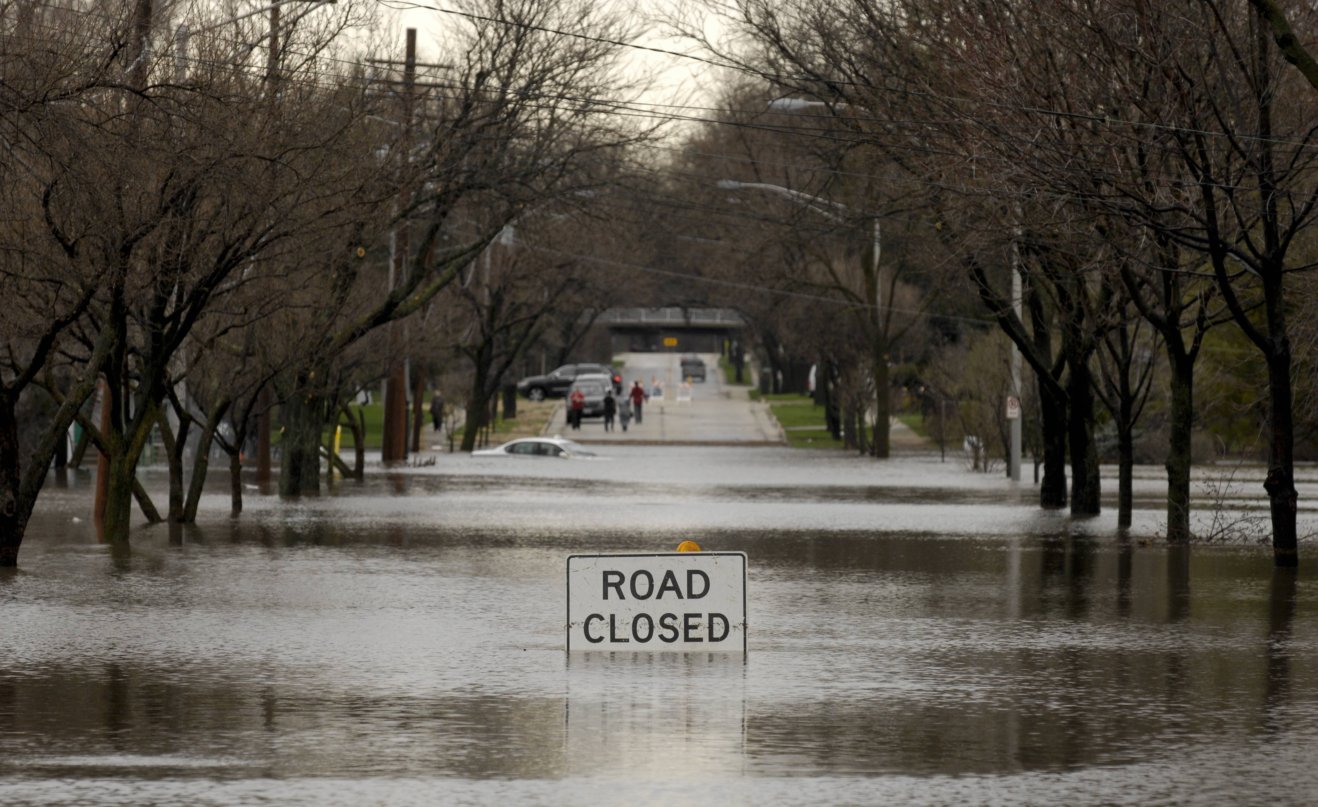 A Road Closed sign is partially submerged along Finley Road at Charles Lane in Lombard Thursday.