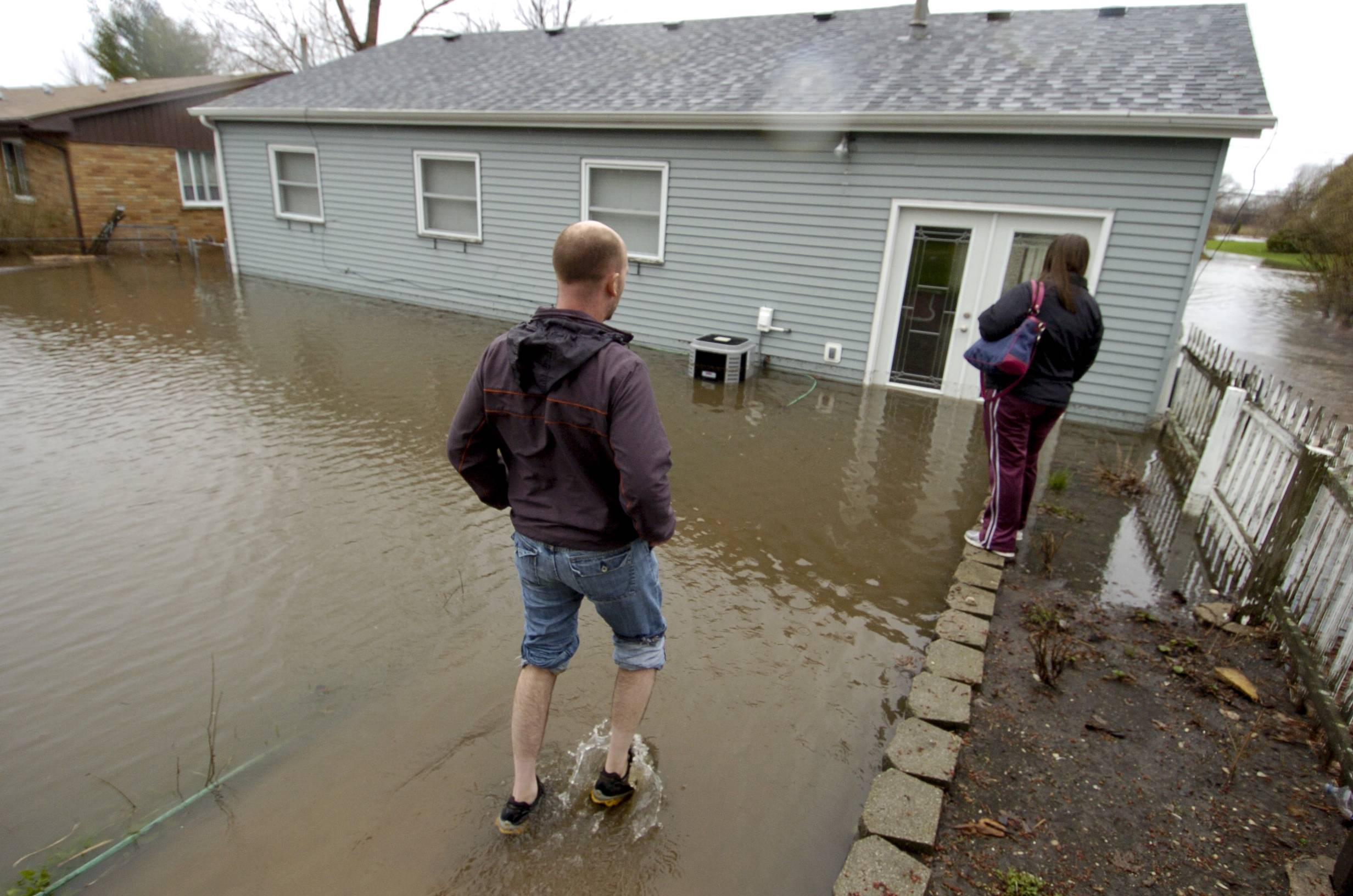Kurt and Debra Langworthy enter their flooded home on Finley Road in Lombard.