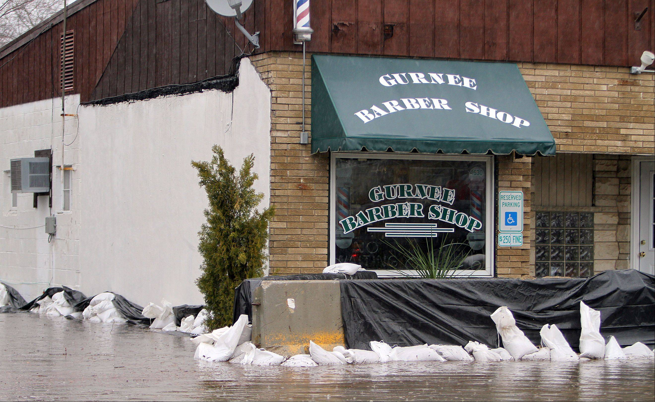 Steve Lundy/slundy@dailyherald.comThe Gurnee Barber Shop Old Grand Avenue prepares for flooding in Gurnee Thursday morning.