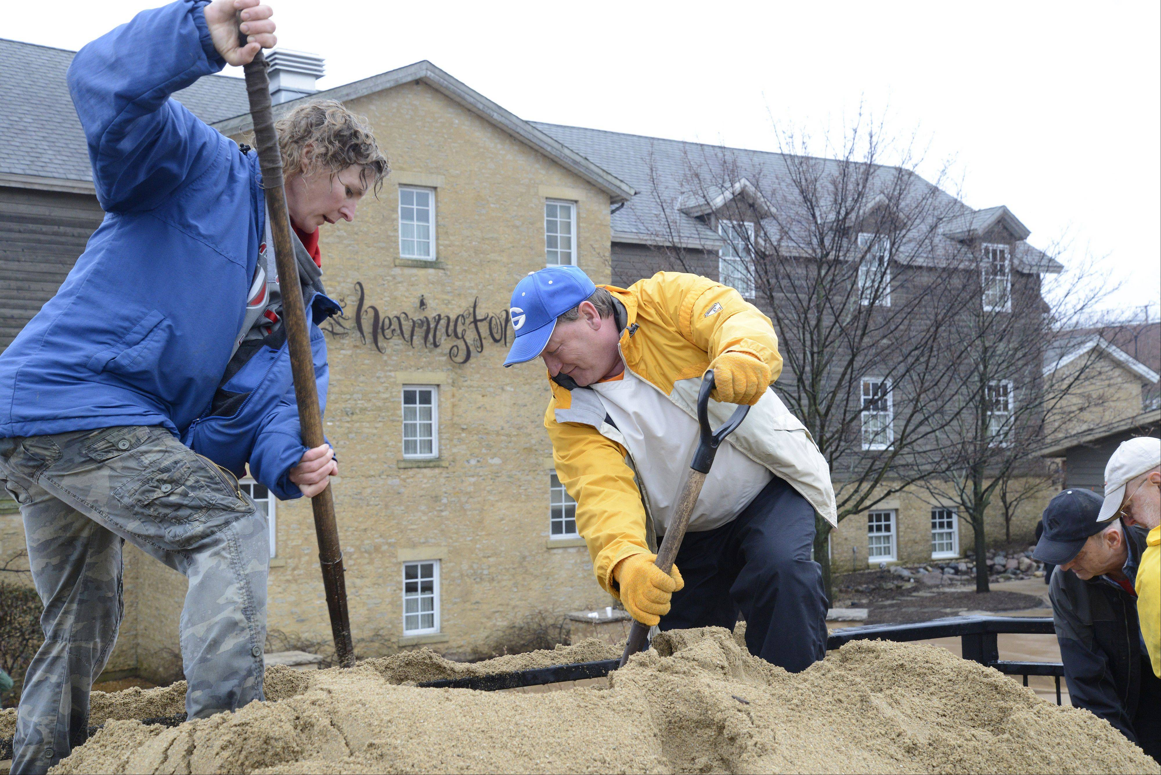 Volunteers Cathy Blaeser of Batavia and Dave Weede of Geneva shovel sand Thursday from the State Street Bridge down to sandbaggers below by the Herrington Inn in Geneva. Paul Ruby, the owner of the Herrington Inn, put out the call for help early in the day and people came by the dozens to help.