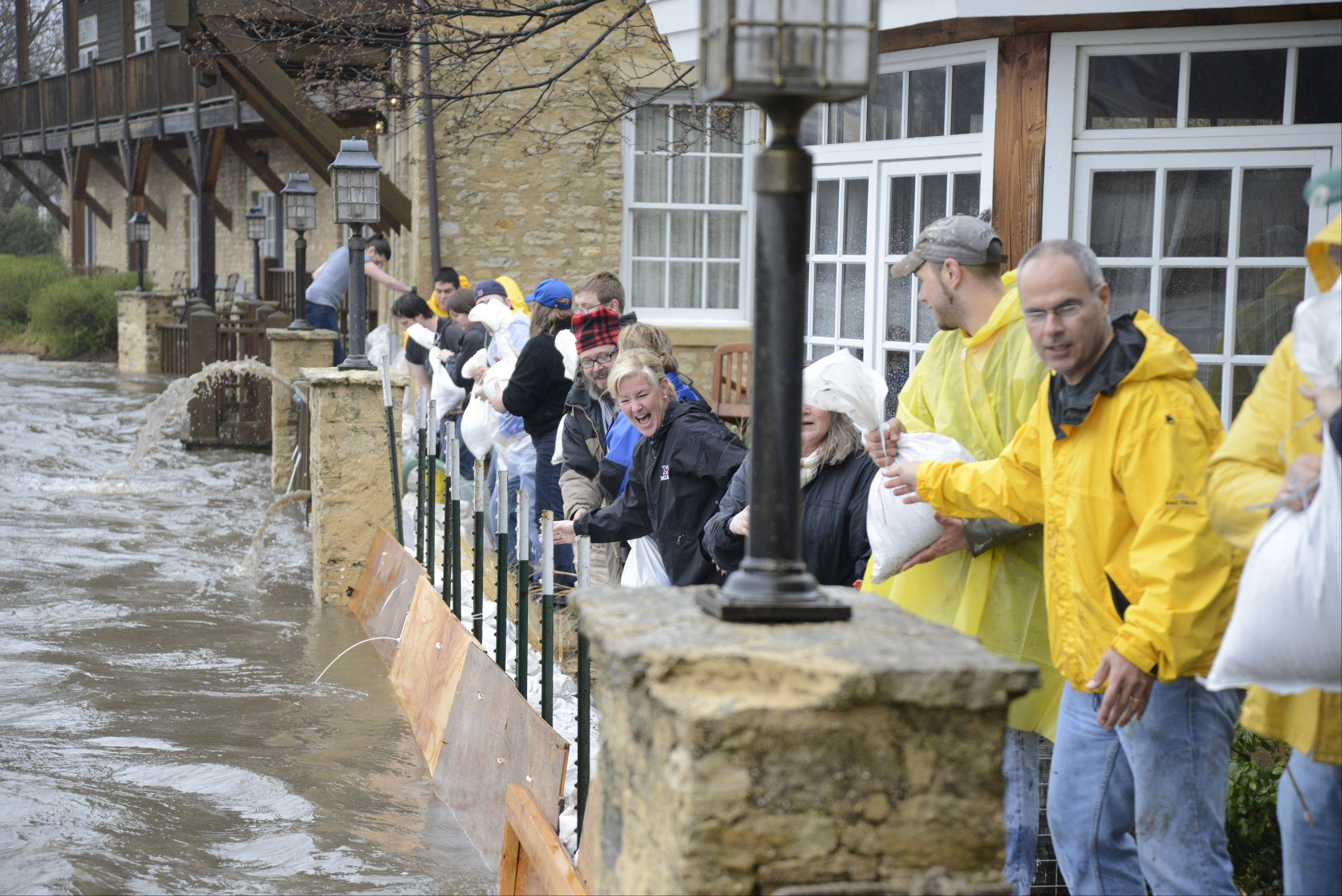 Volunteers stack sandbags Thursday at the waterline by the Herrington Inn in Geneva.