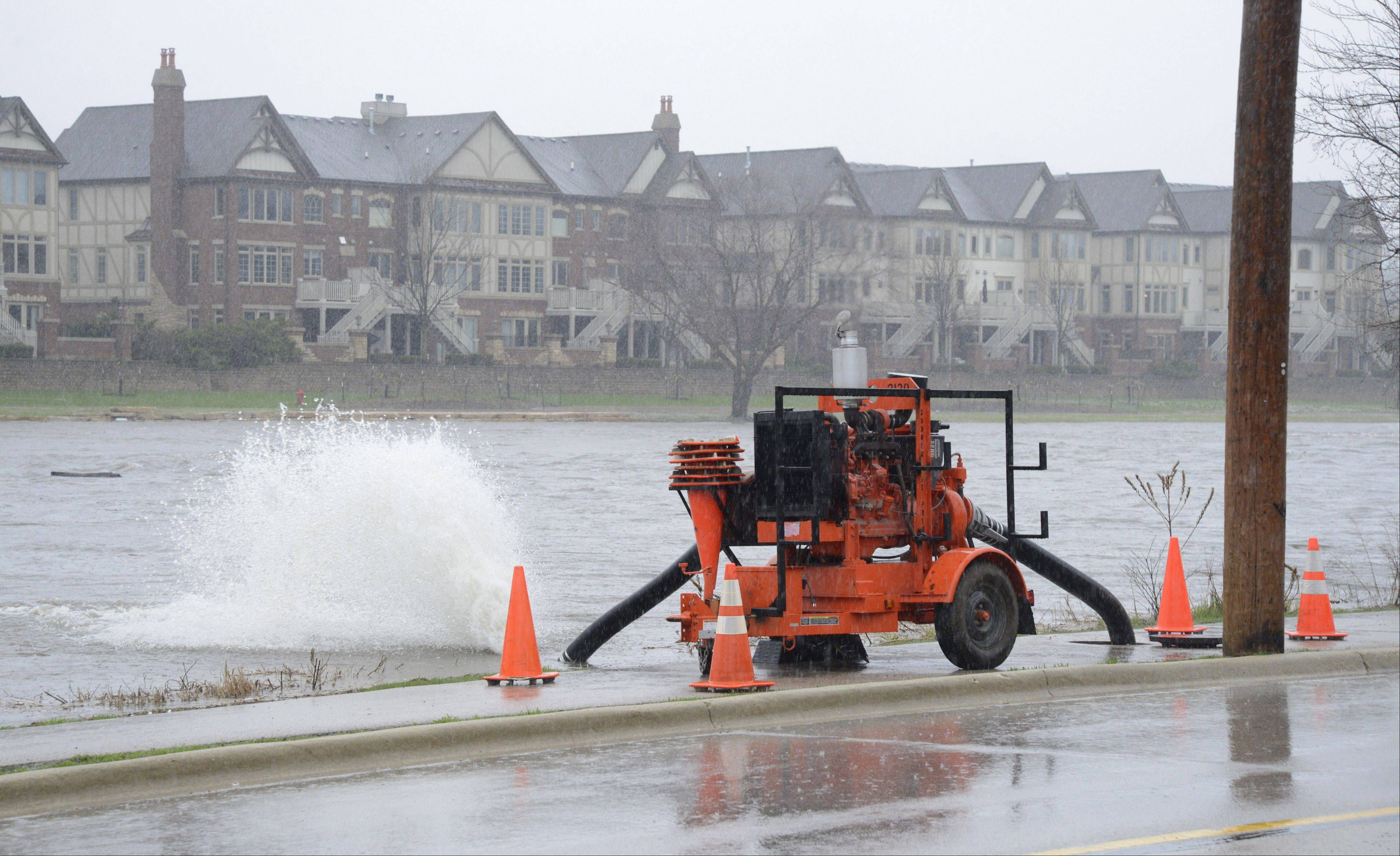 Water shoots out of a hose line dropped into a sewer to eject excess rainfall Thursday into the Fox River along the pedestrian path on Route 25 in St. Charles.