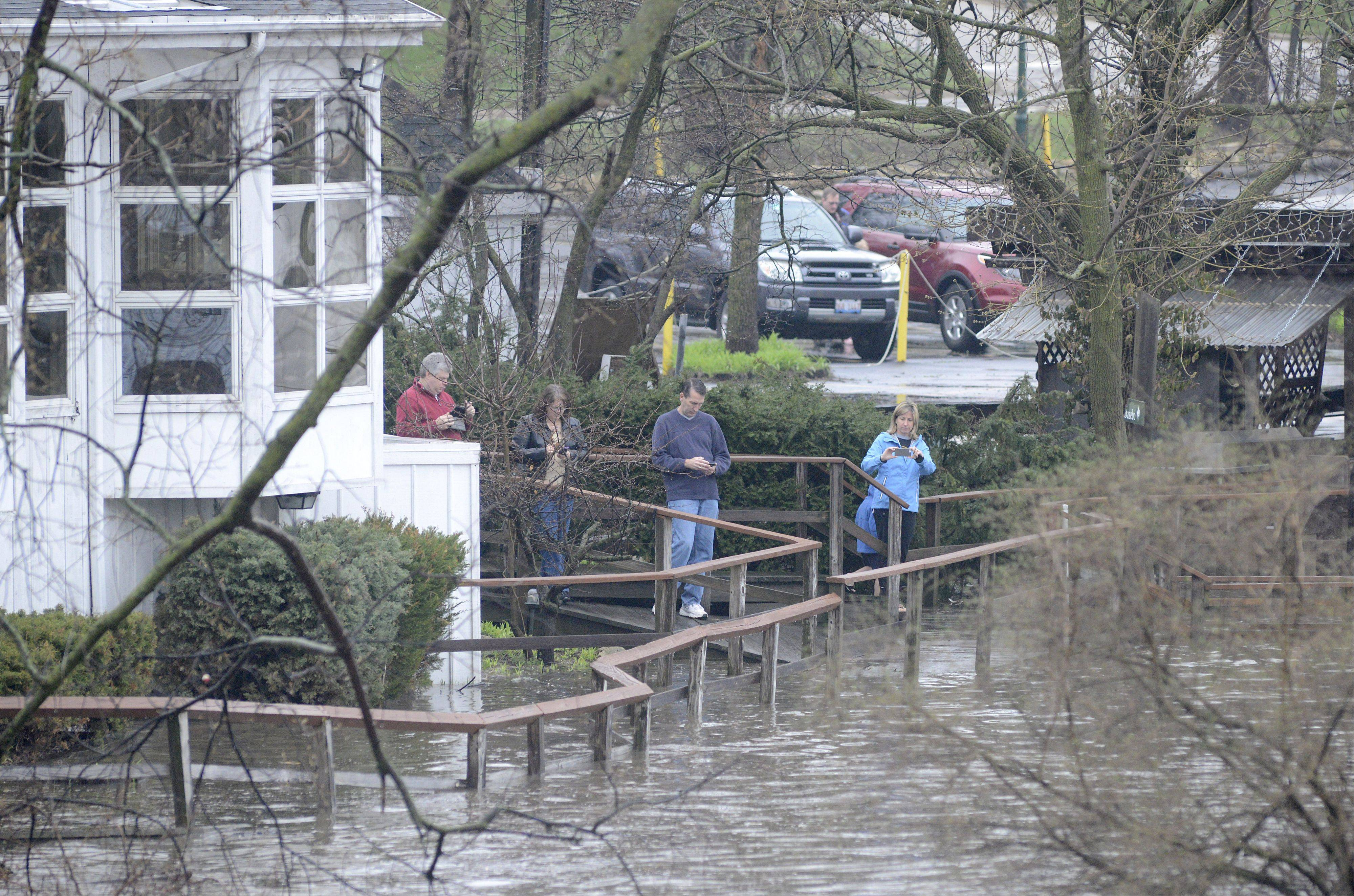 People gather on the boardwalk outside the shuttered Mill Race Inn next to Island Park in Geneva Thursday to photograph the floodwaters. A constant flow of cars went in and out of the parking lot to get a glimpse of the racing waters.