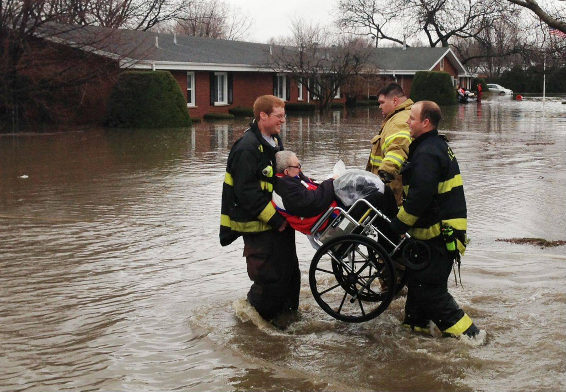 Rescuers carry a resident of the Snow Valley Nursing and Rehabilitation Center in Lisle to safety after floodwaters threatened the facility.