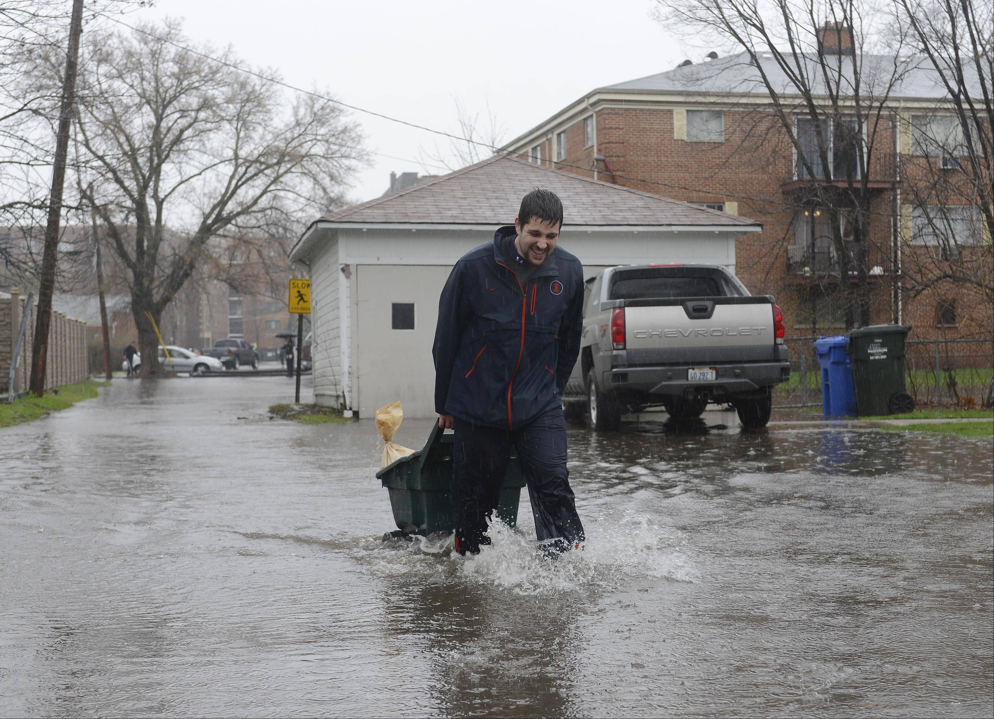 Dan Bachar of Des Plaines wheels a cart loaded with sandbags to his parents' house on Walnut Avenue as floodwaters rise in Des Plaines Thursday.