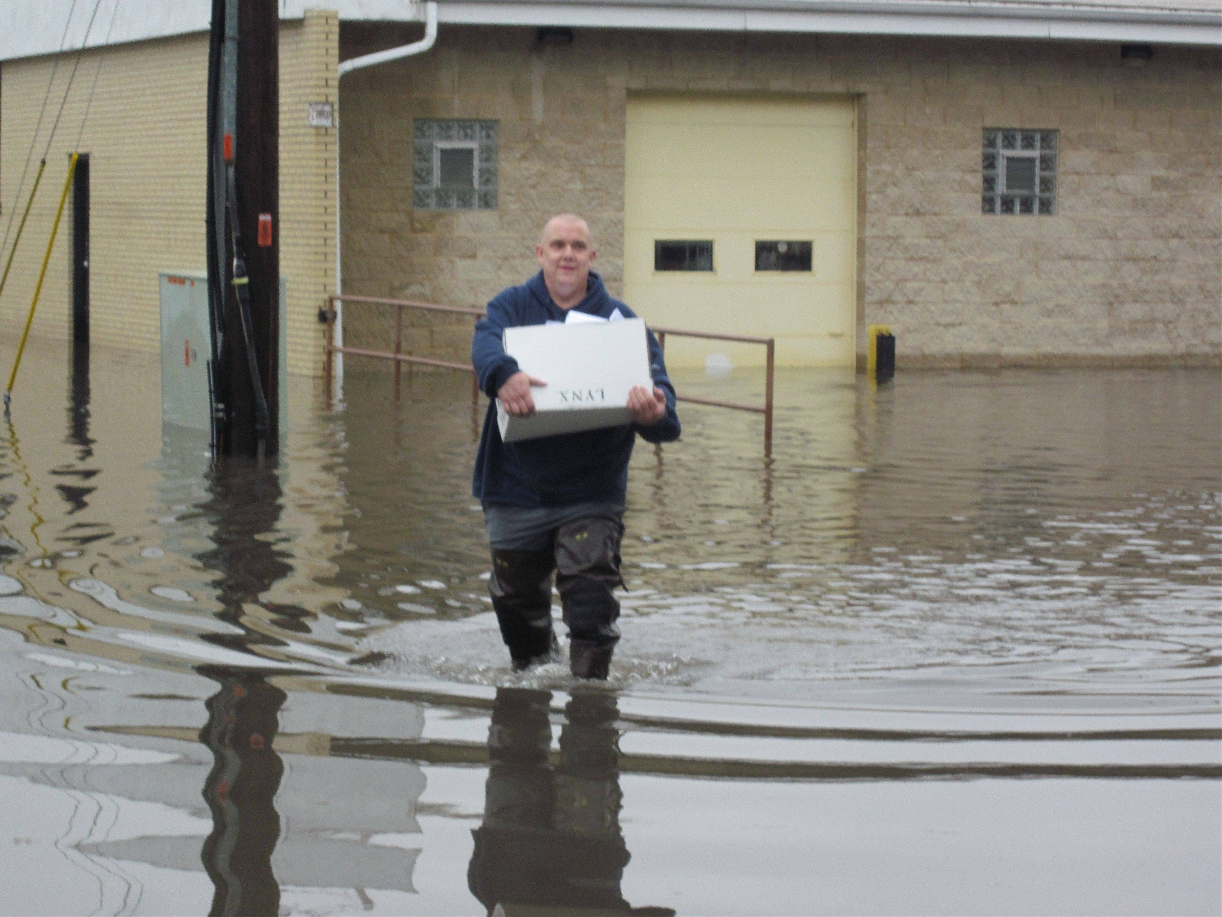 Ed Davidson, owner of CopySetCenter on Oakton Street in Des Plaines, carries part of a printing order out of his flooded business and across his flooded loading dock area to the waiting car of Jim Carlson of R.J. Printing in Mundelein.