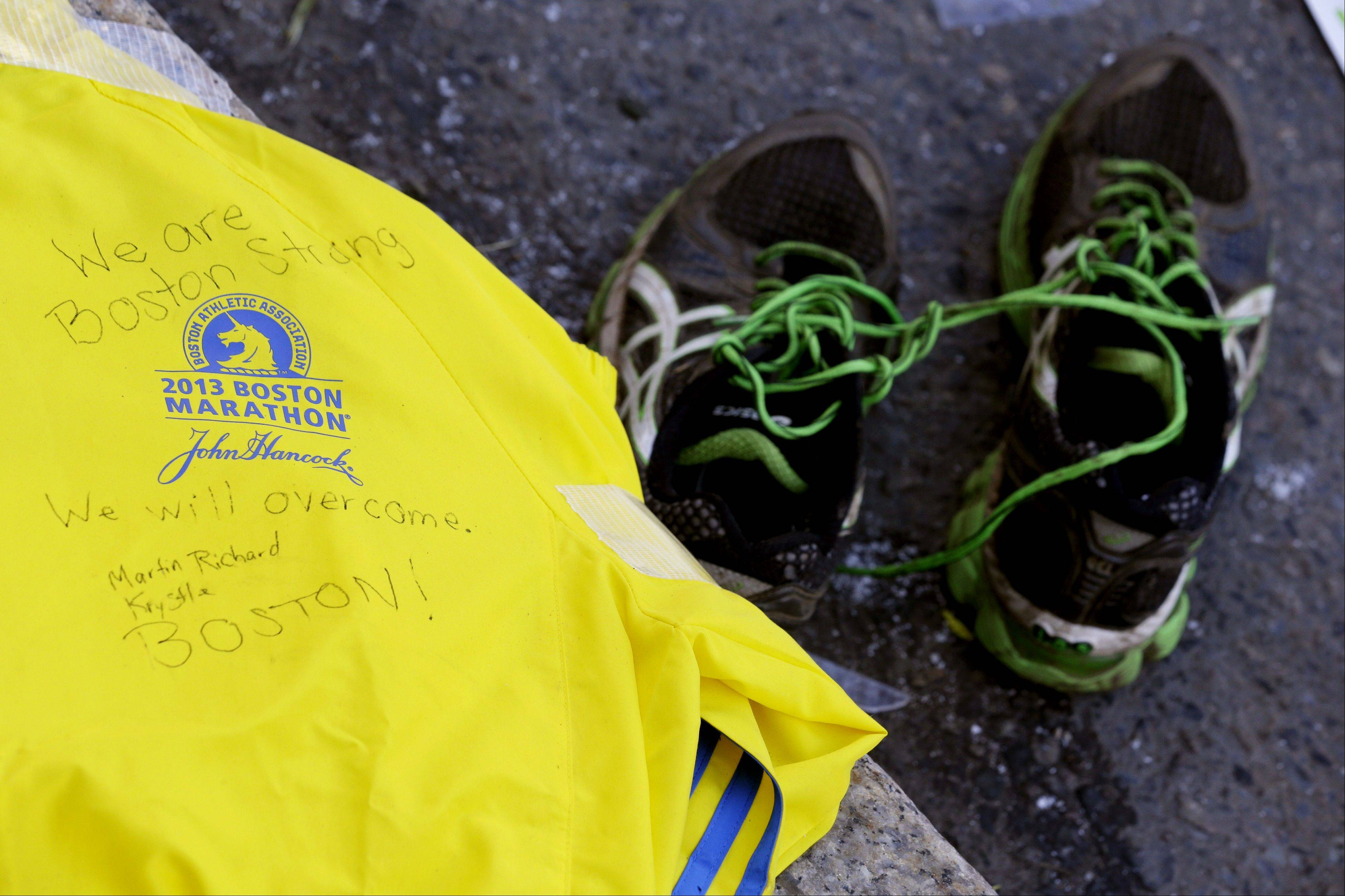 A message is written on a volunteer's jacket near running shoes at a makeshift memorial on Boylston Street near the blast site of the Boston Marathon explosions, Thursday, April 18, 2013, in Boston. The city continues to cope following Monday's explosions near the finish line of the marathon.