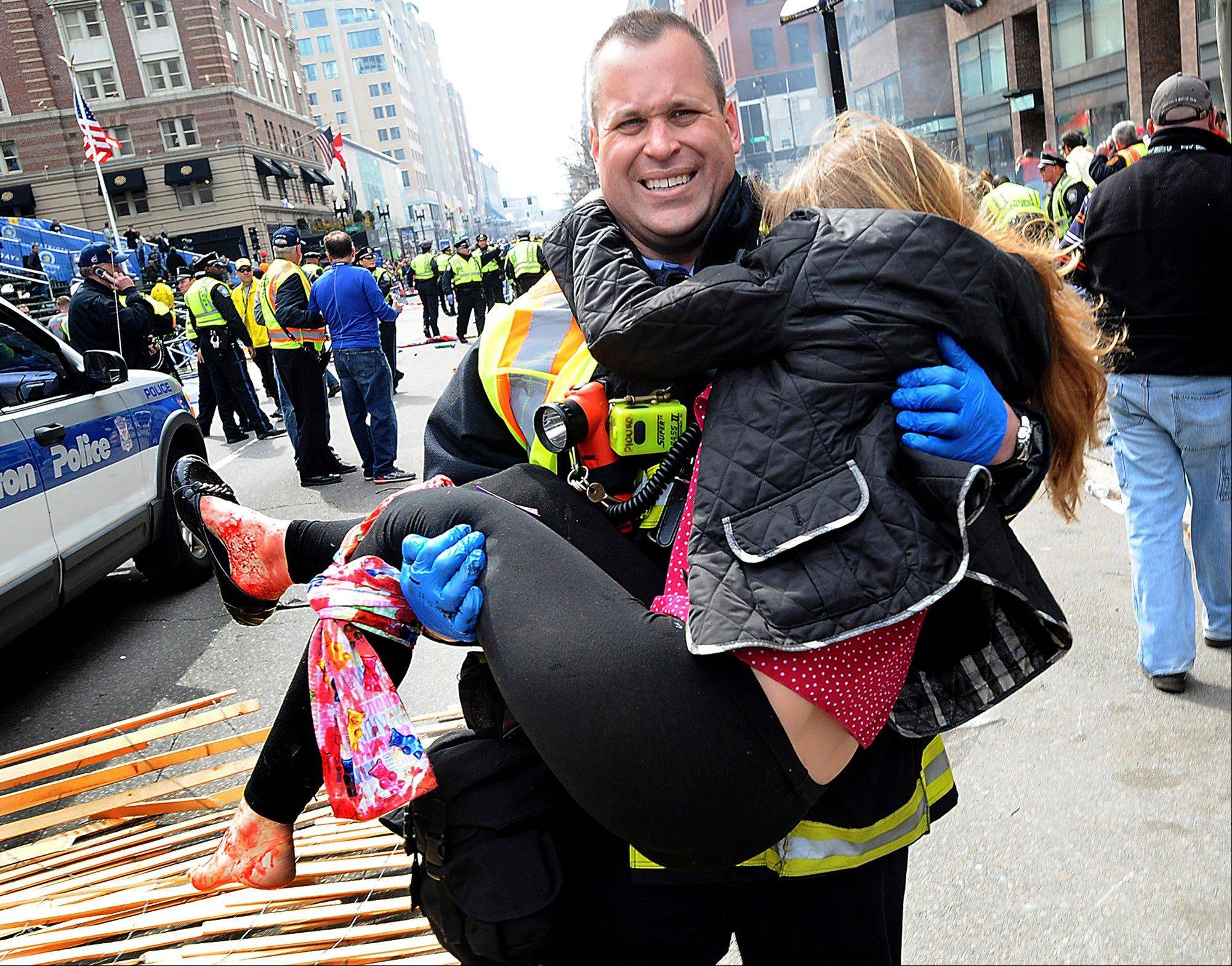 Boston Firefighter James Plourde carries an injured girl away from the scene after a bombing near the finish line of the Boston Marathon in Boston.