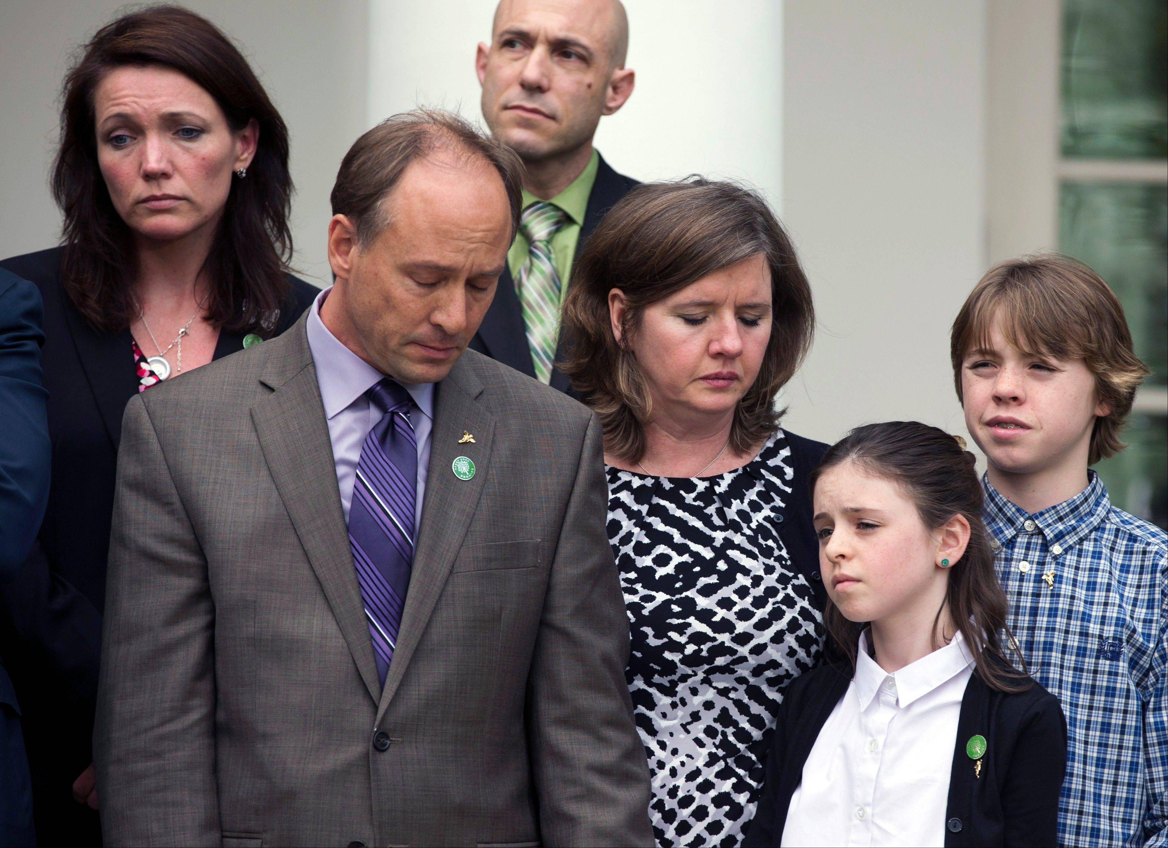 Family members of those lost in the Newtown, Conn. school shooting, Mark and Jackie Barden, with their children Natalie and James, who lost Daniel; Nicole Hockley, mother of Dylan, upper left, and Jeremy Richman, father of Avielle in the back, stand together as President Barack Obama speaks in the Rose Garden of the White House, Wednesday, April 17, 2013, in Washington. Obama spoke about measures to reduce gun violence and a bill to expand background checks on guns that was defeated in the Senate.