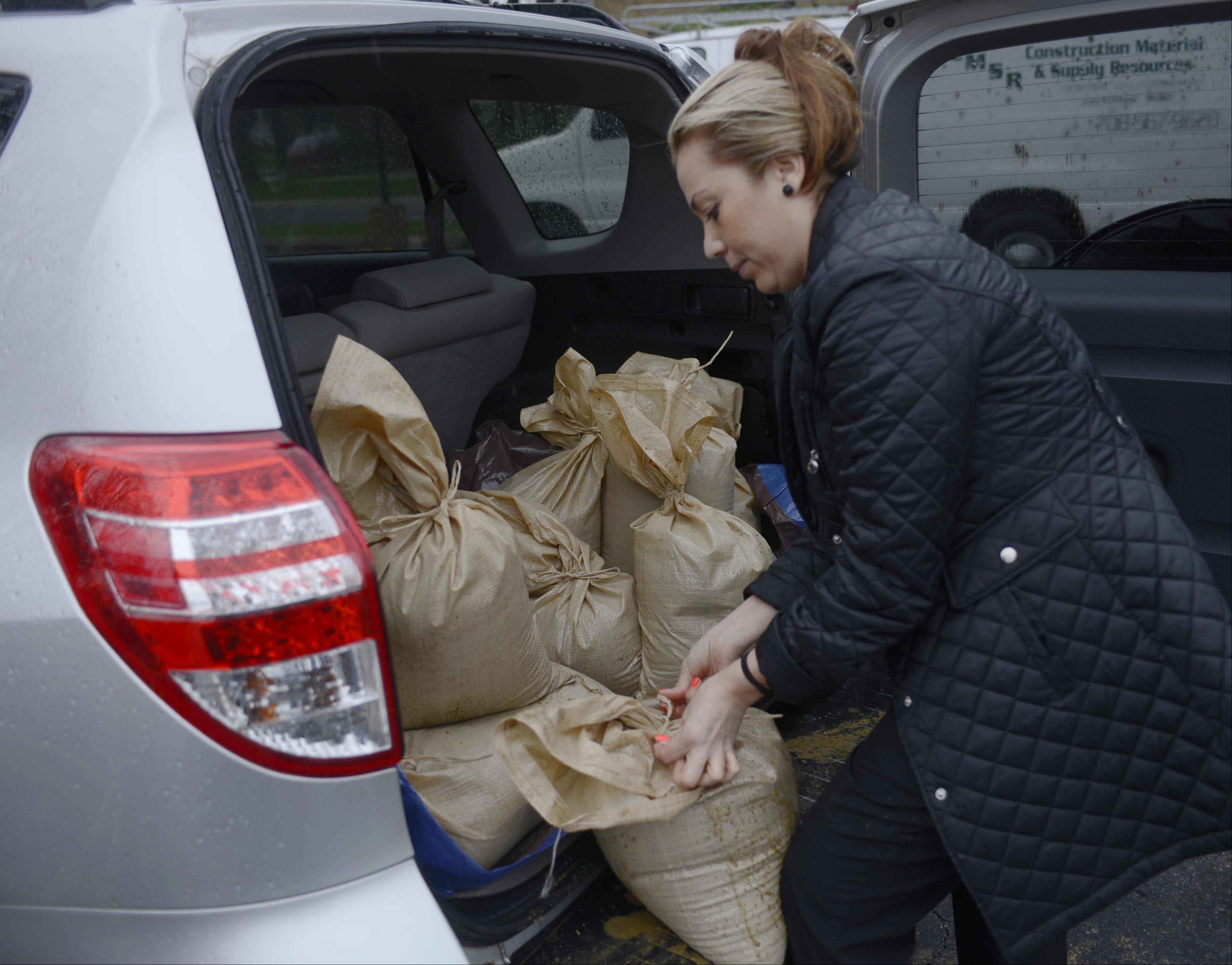 Martha Martinez ties sandbags loaded in the back of her van at the Christ Church parking lot as floodwaters rise in Des Plaines Thursday.