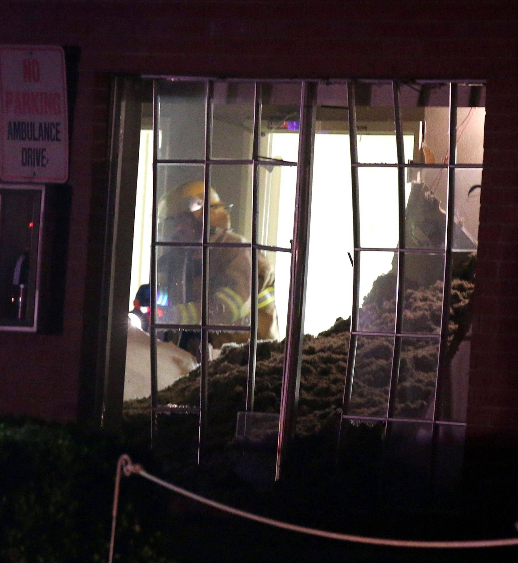 A firefighter searches a nursing home that was damaged after an explosion at a neary by fertilizer plant Wednesday.