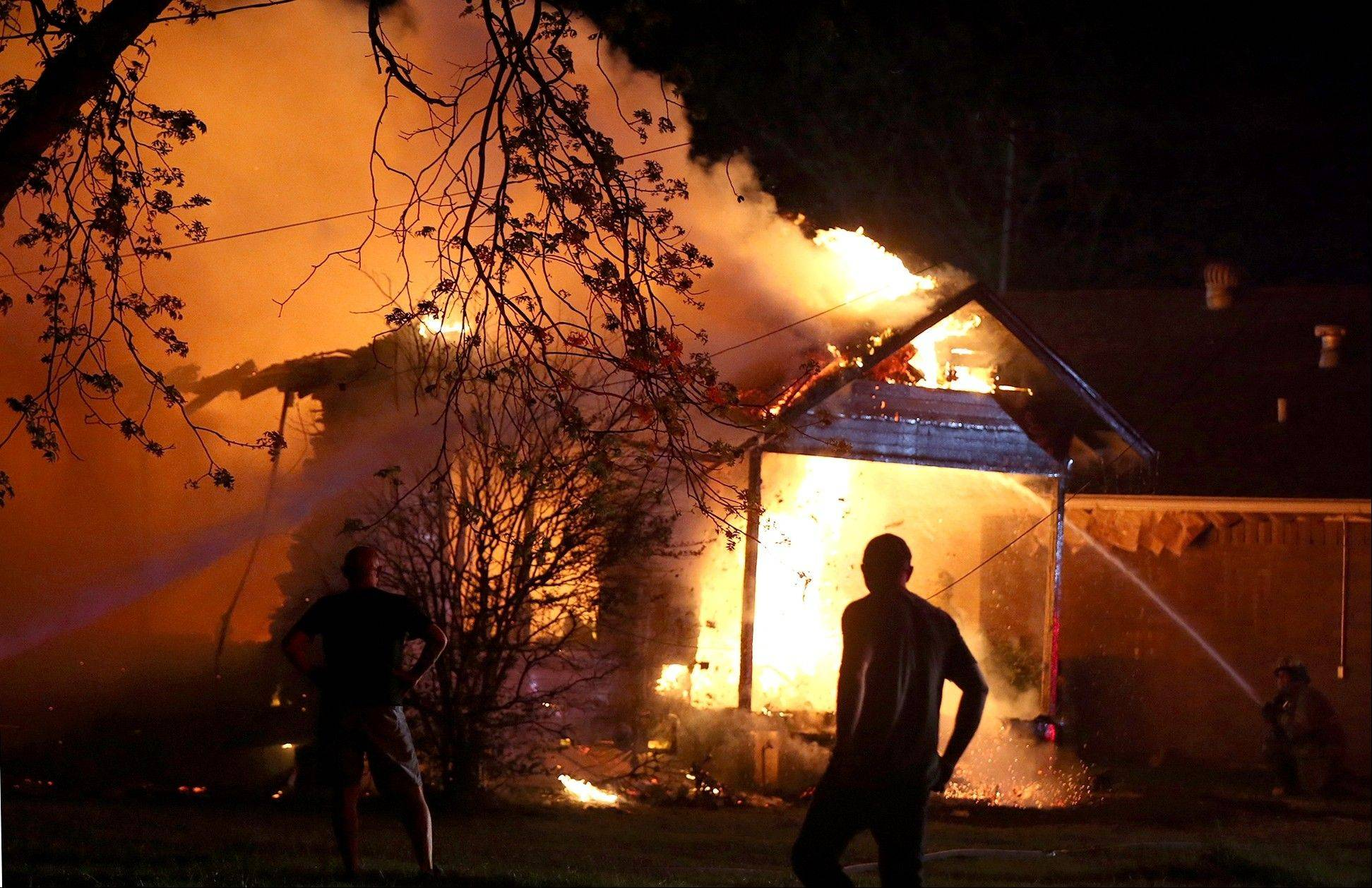 A person looks on as emergency workers fight a house fire after a near by fertilizer plant exploded.