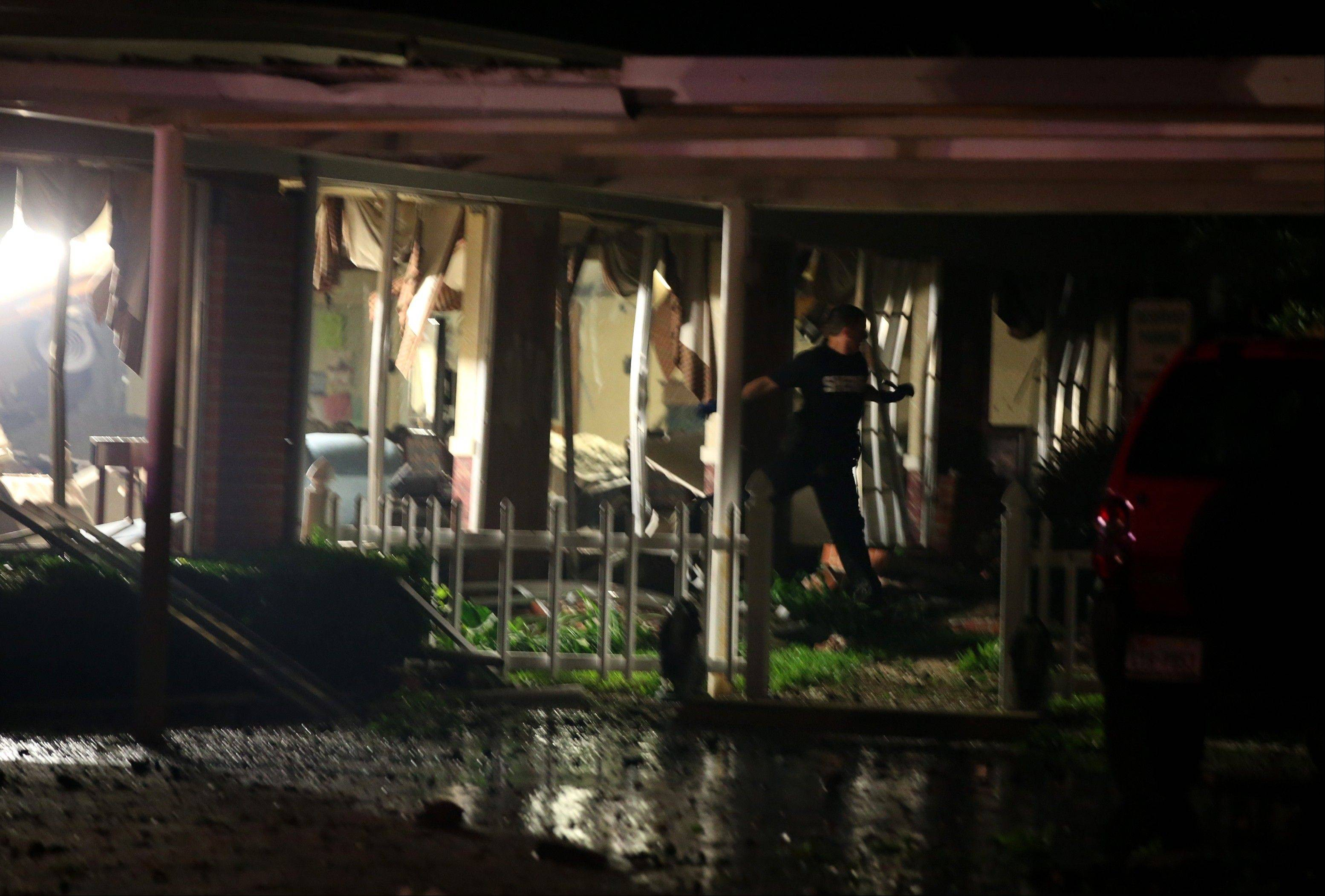 An emergency worker walks through damaged apartment building after the fertilizer plant explosion Wednesday.