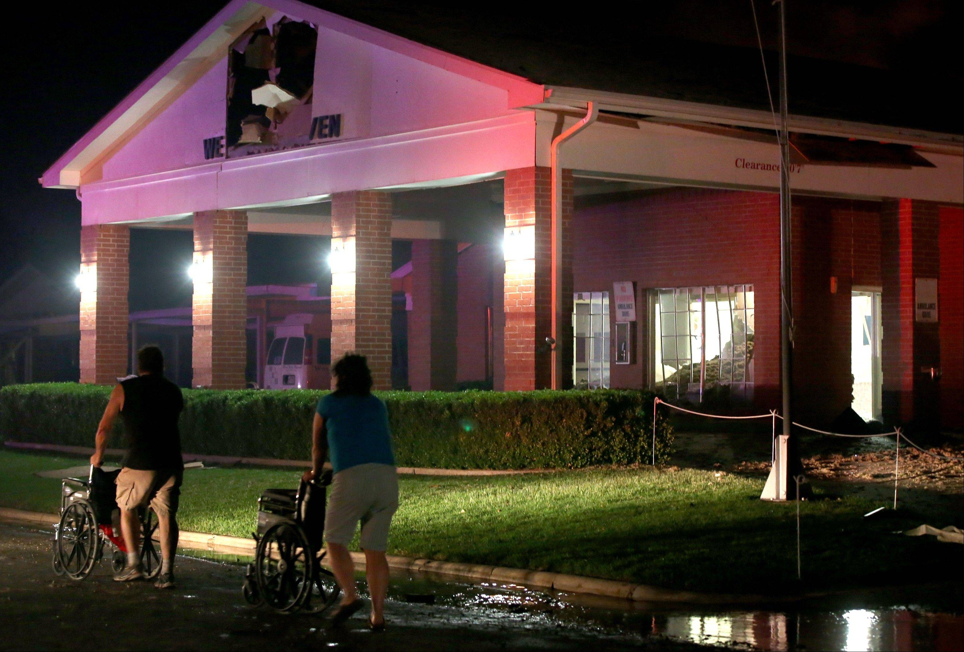 People are seen pushing wheelchairs in front of a damaged nursing home after an explosion at a nearby fertilizer plant.