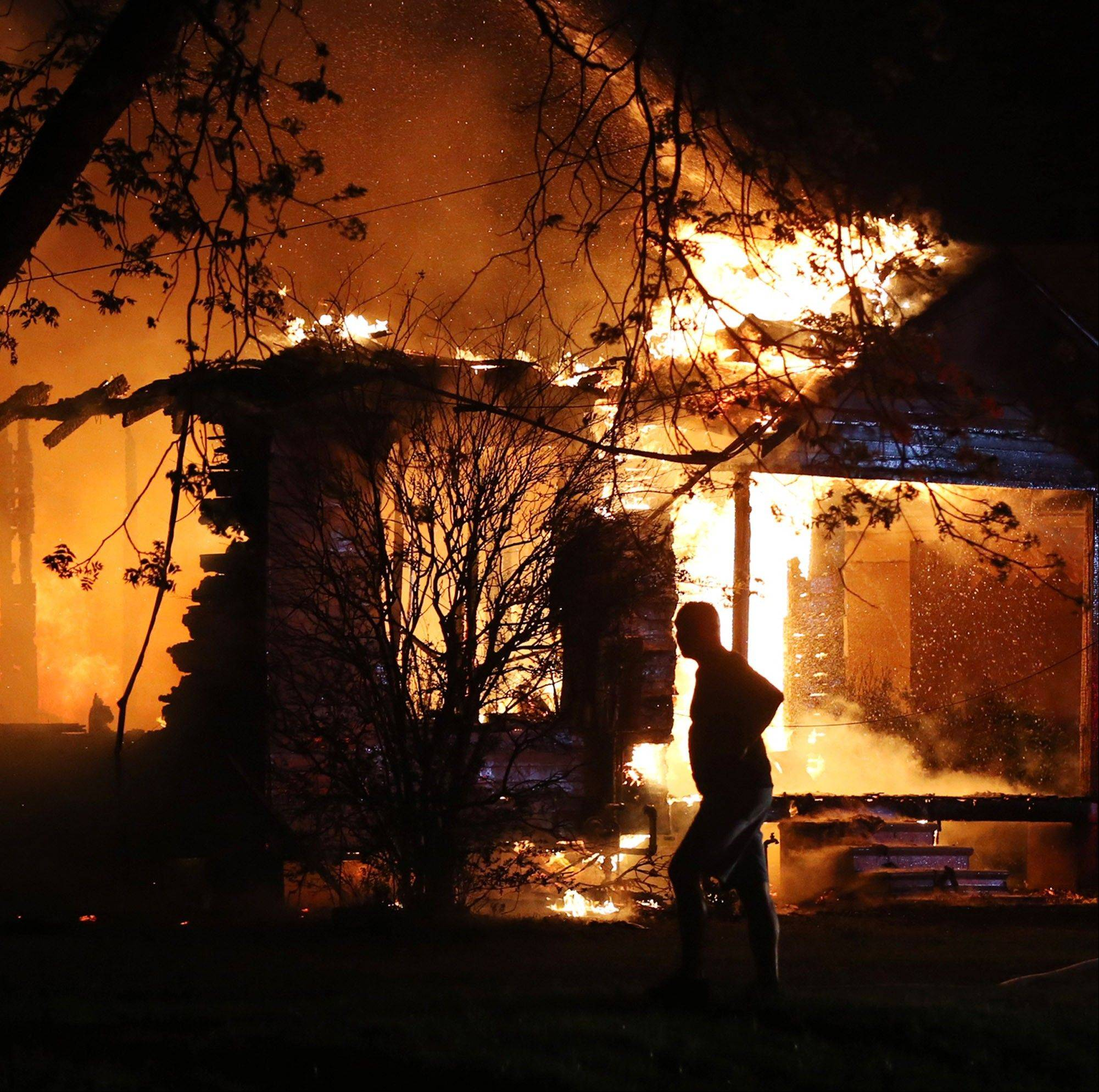 A person looks on as emergency workers fight a house fire after a nearby fertilizer plant exploded Wednesday.