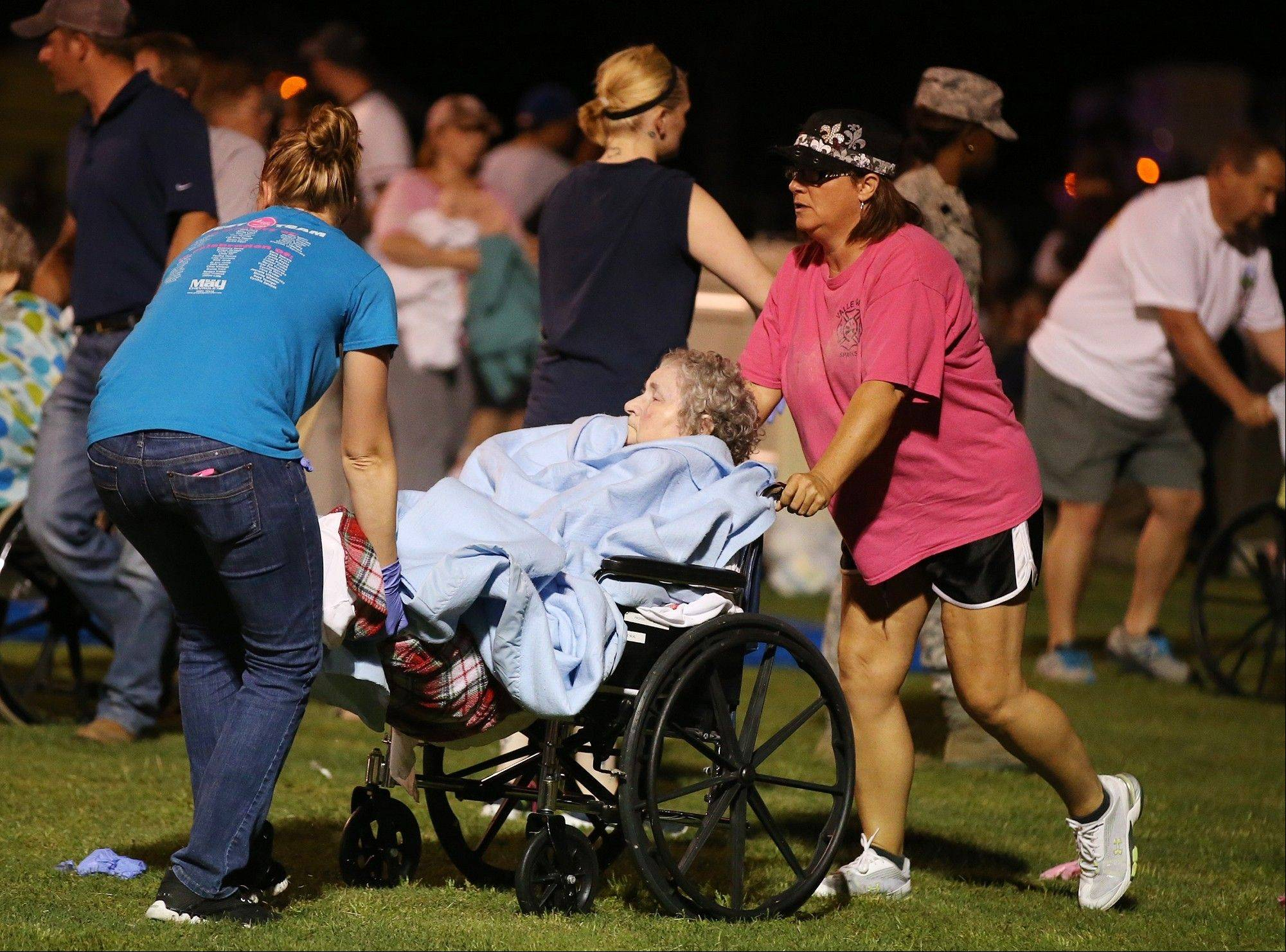 An elderly person is assisted at a staging area at a local school stadium following an explosion at a fertilizer plant Wednesday in West, Texas. An explosion at a fertilizer plant near Waco caused numerous injuries and sent flames shooting high into the night sky on Wednesday.