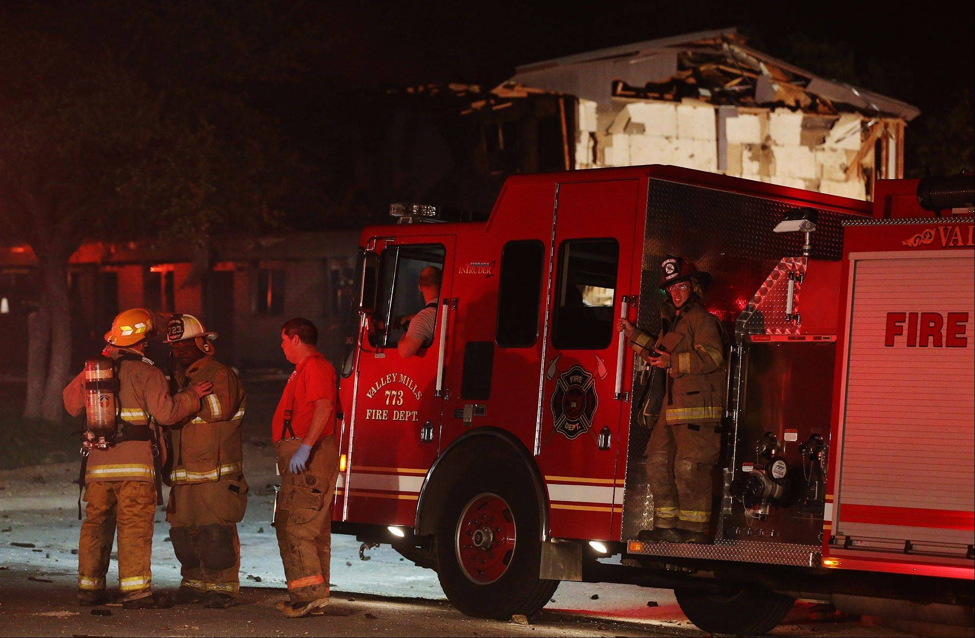 Rescue workers gather near a damaged apartment complex after a nearby fertilizer plant exploded Wednesday.
