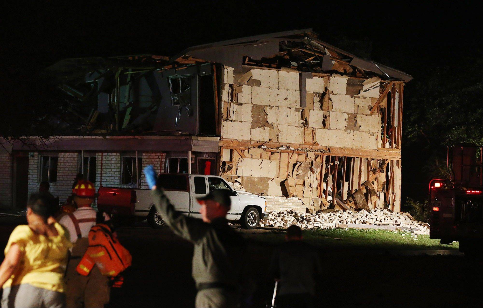 Rescue workers work near a damaged apartment complex after a nearby fertilizer plant exploded Wednesday.